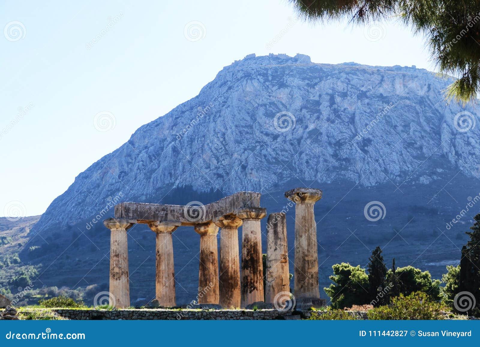 Άποψη του φρουρίου Acrocorinth από αρχαίο Corinth, Ελλάδα με τους στυλοβάτες του ναού απόλλωνα στο πρώτο πλάνο