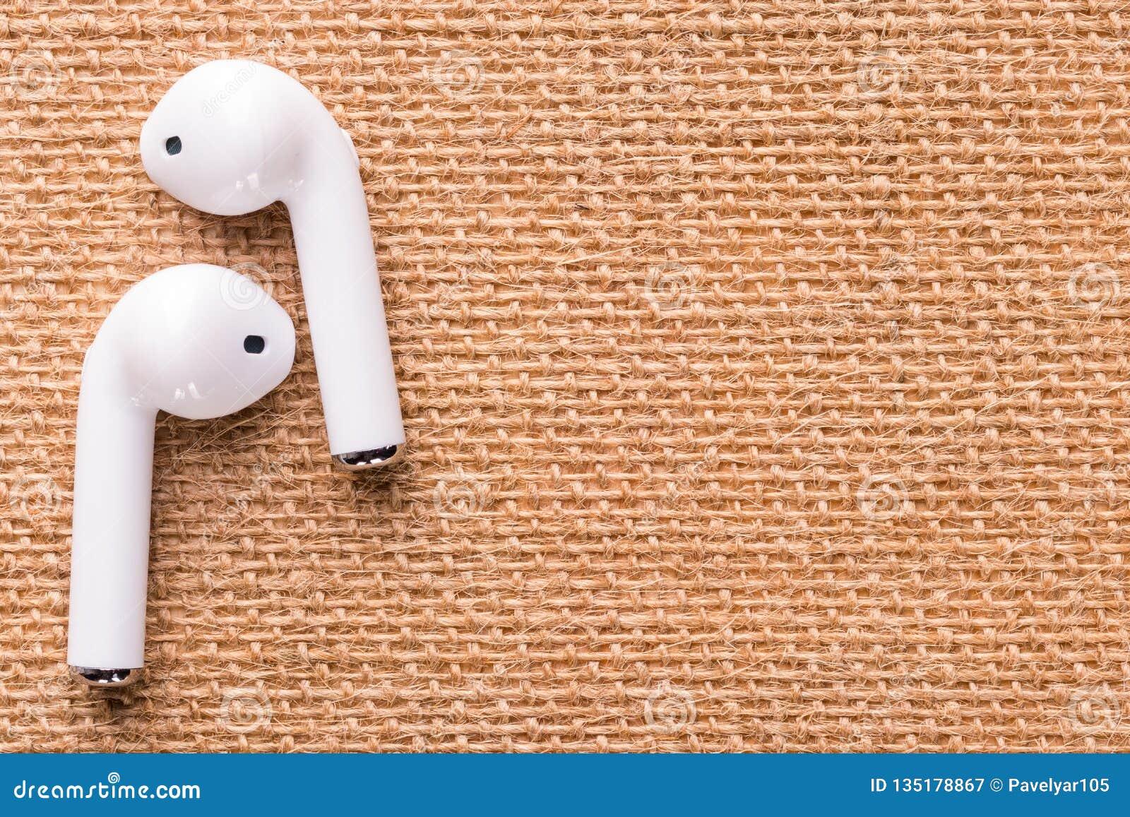 Άσπρα ασύρματα ακουστικά σε μια όμορφη ψάθινη πετσέτα