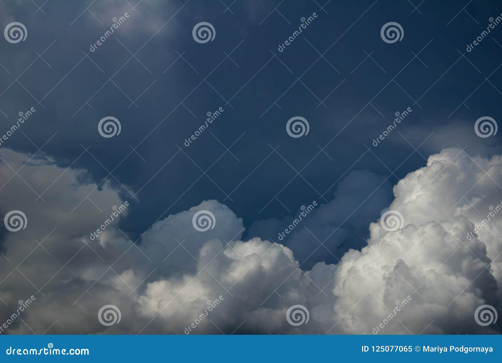 Άσπρα θολωμένα σύννεφα σωρειτών στο σκούρο μπλε ουρανό πριν από τη θύελλα