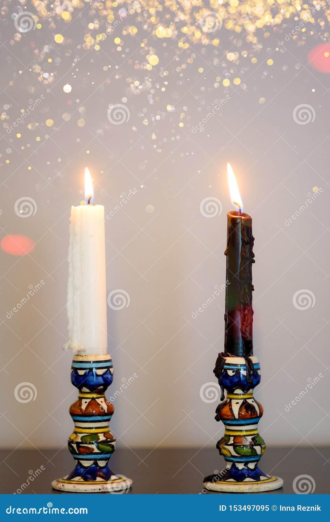 Άσπρα και μαύρα κεριά Δύο καίγοντας κεριά στον ξύλινο πίνακα ενάντια στον γκρίζο τοίχο