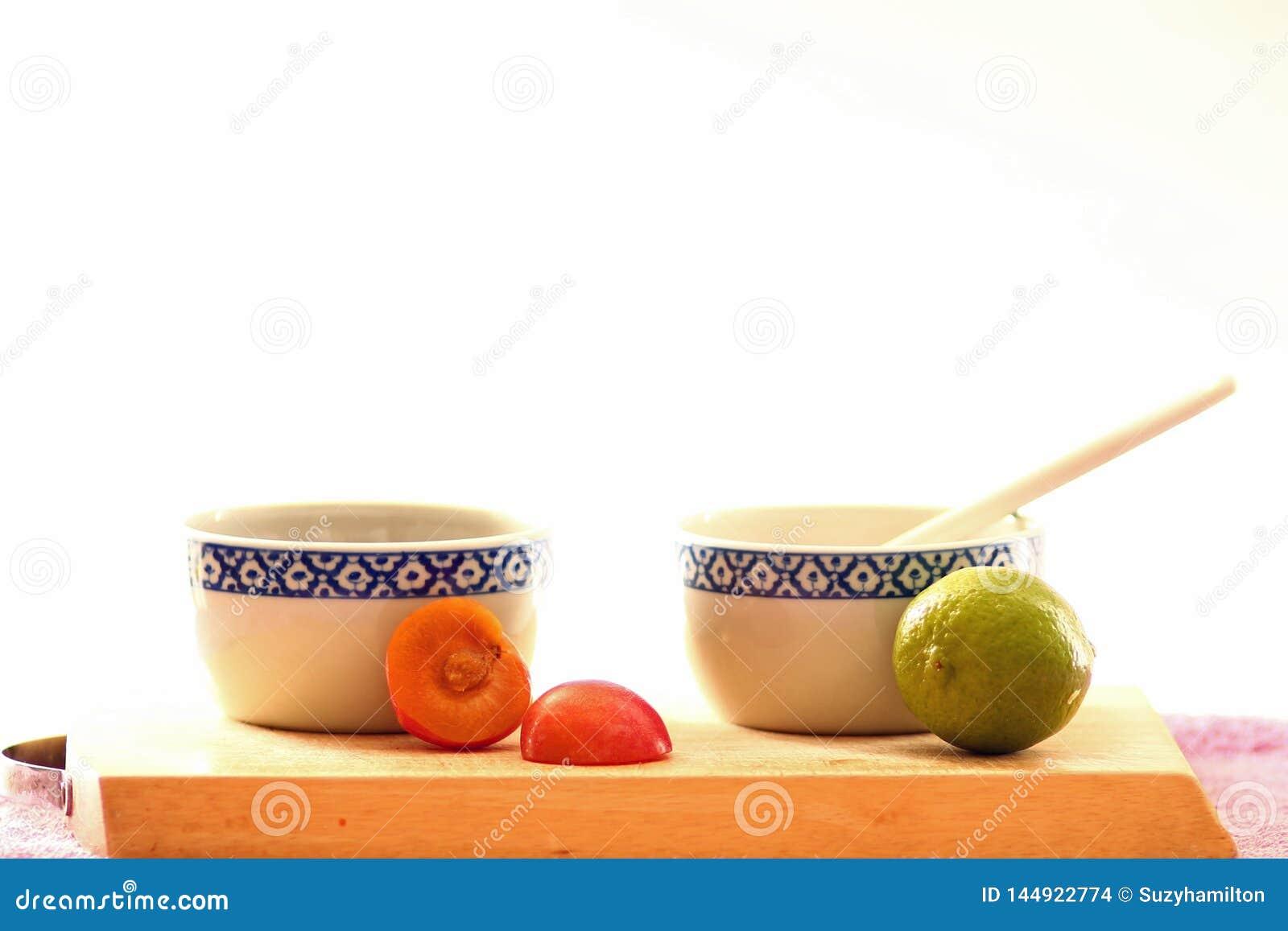 Άσπρα και μπλε κύπελλα με τα καρύδια και σπόροι στον ξύλινο πίνακα