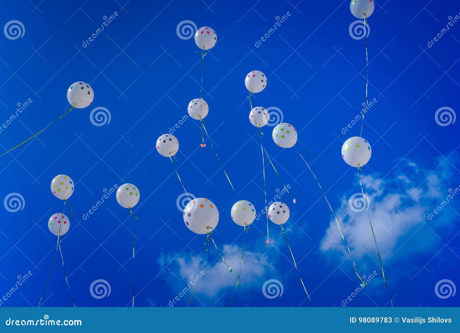 Άσπρα μπαλόνια στο μπλε ουρανό