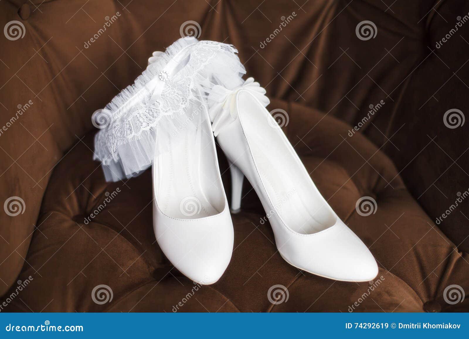840fa9652eee Άσπρα νυφικά παπούτσια με garter στο καφετί υπόβαθρο. Περισσότερες  παρόμοιες στοκ εικόνες