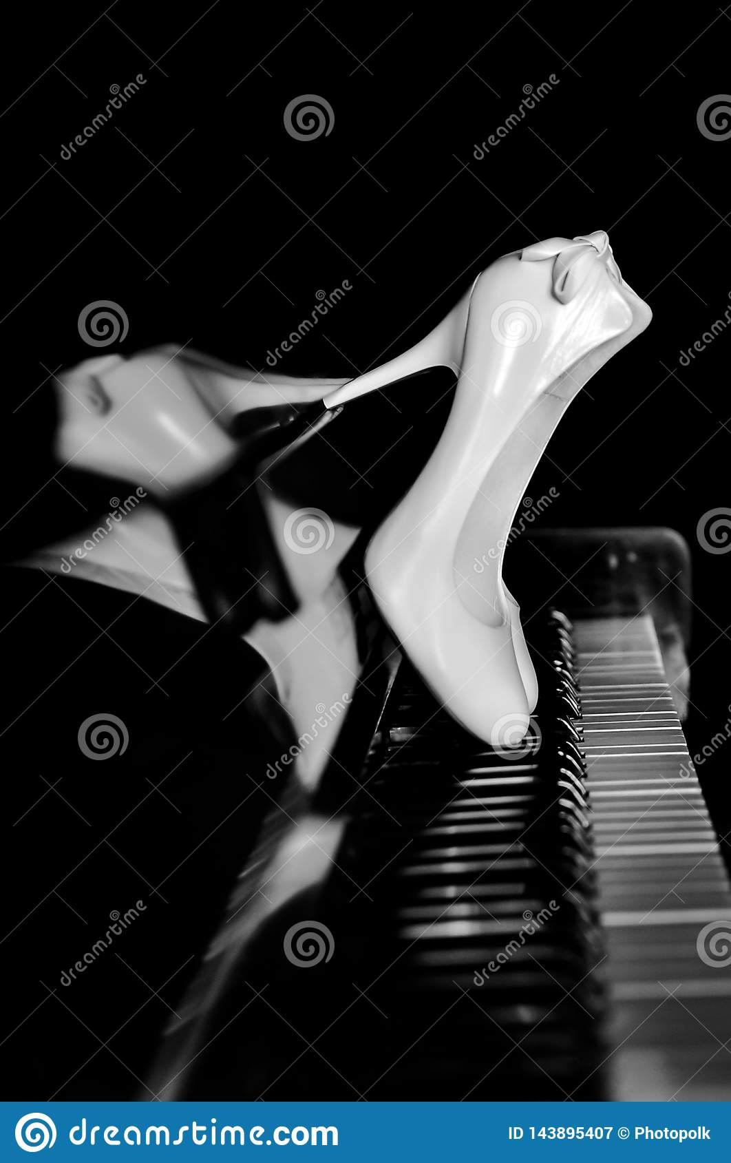 Άσπρα παπούτσια της νύφης στα κλειδιά πιάνων