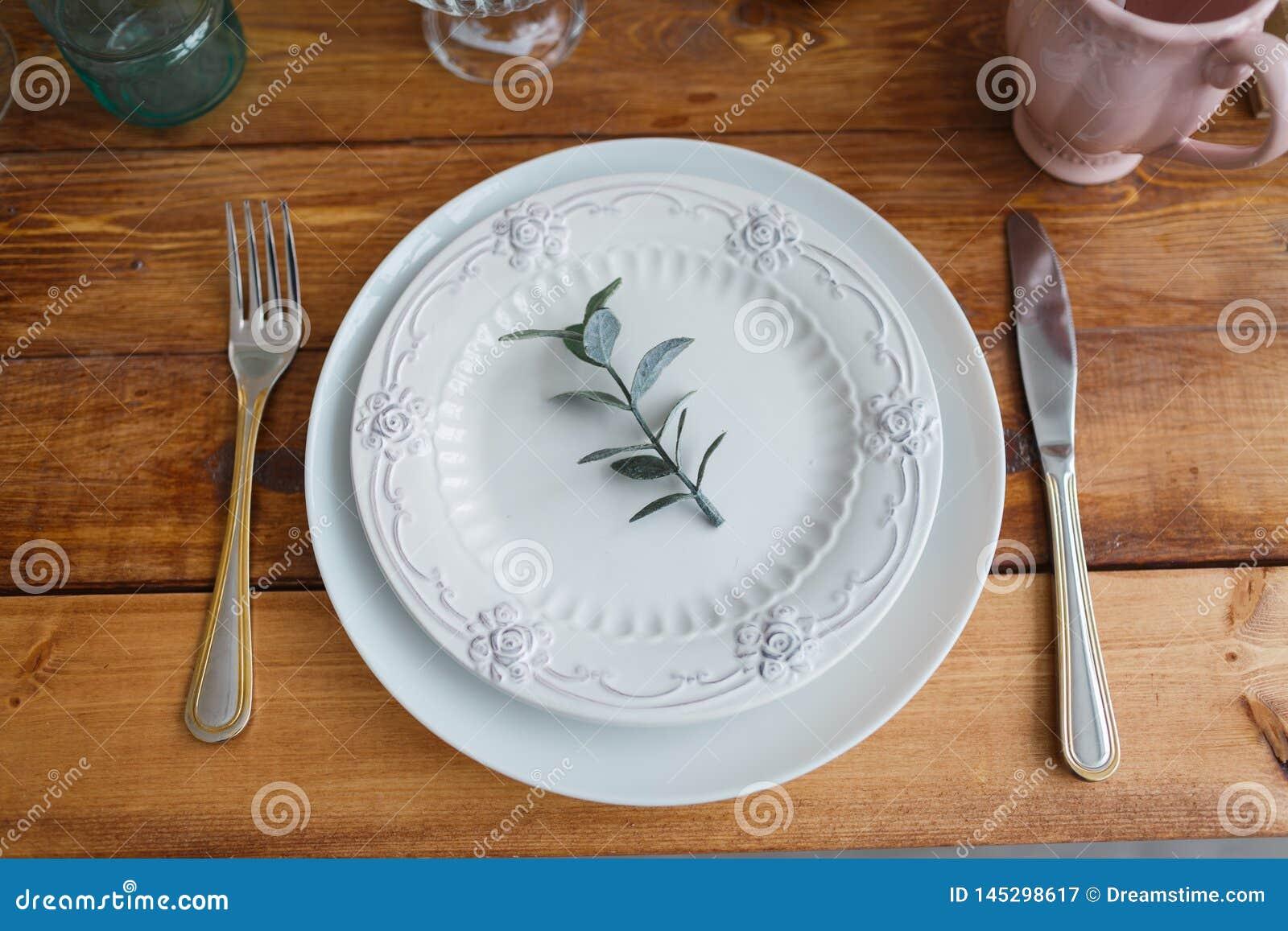 Άσπρα πιάτα στον ξύλινο πίνακα