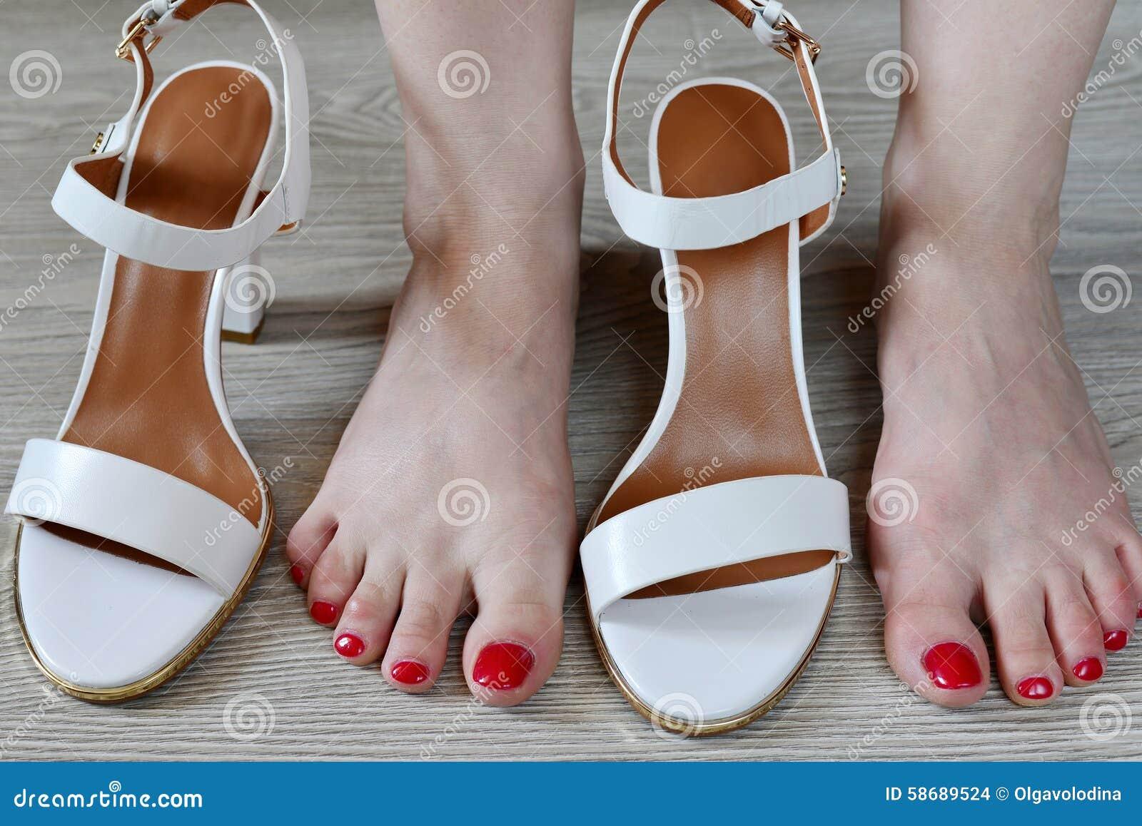 Άσπρα σανδάλια γυναικών πόδια και