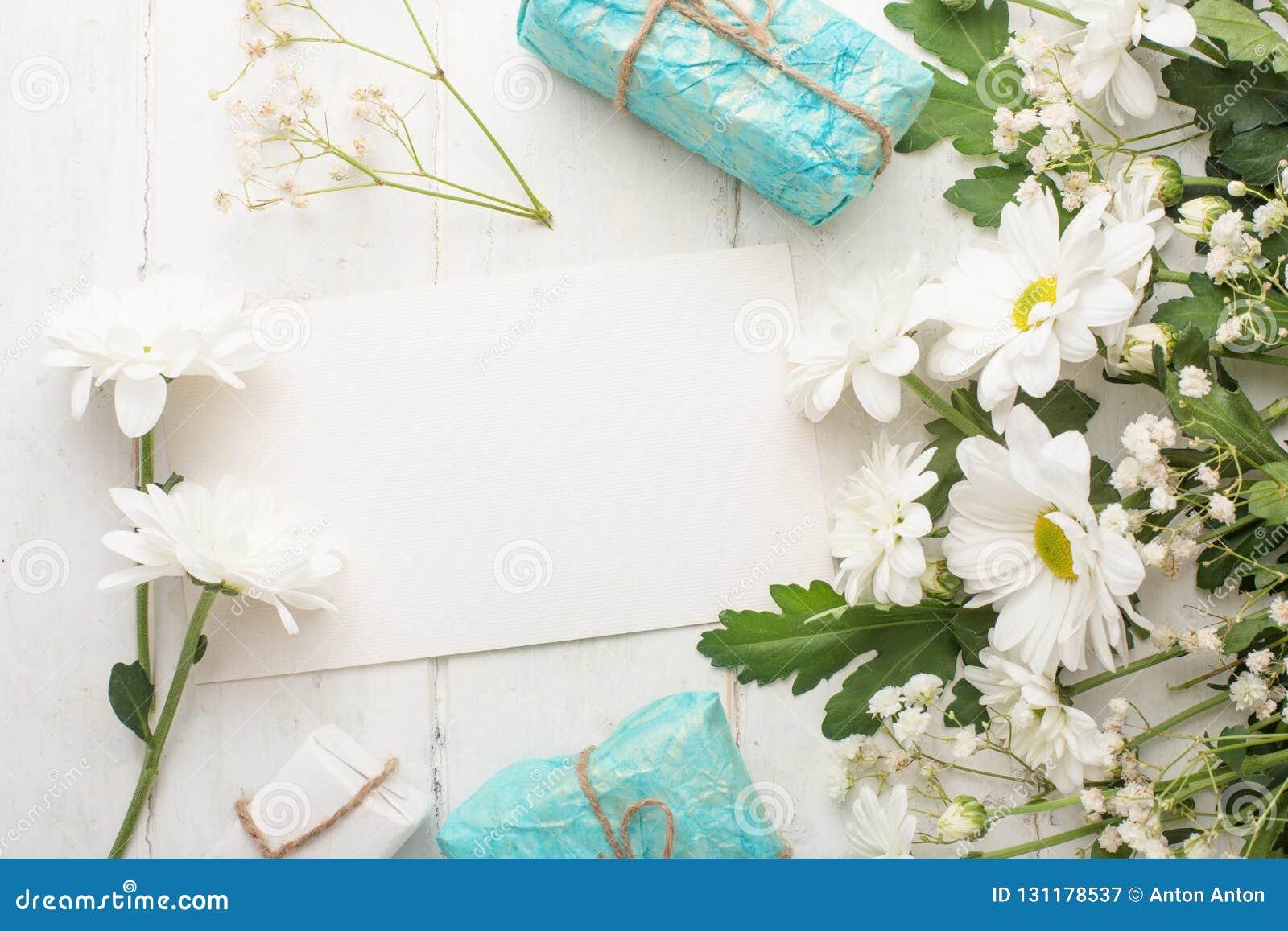 Άσπρα χρυσάνθεμα με τα δώρα σε ένα άσπρο ξύλινο υπόβαθρο, με το κενό διάστημα για το γράψιμο ή τη διαφήμιση