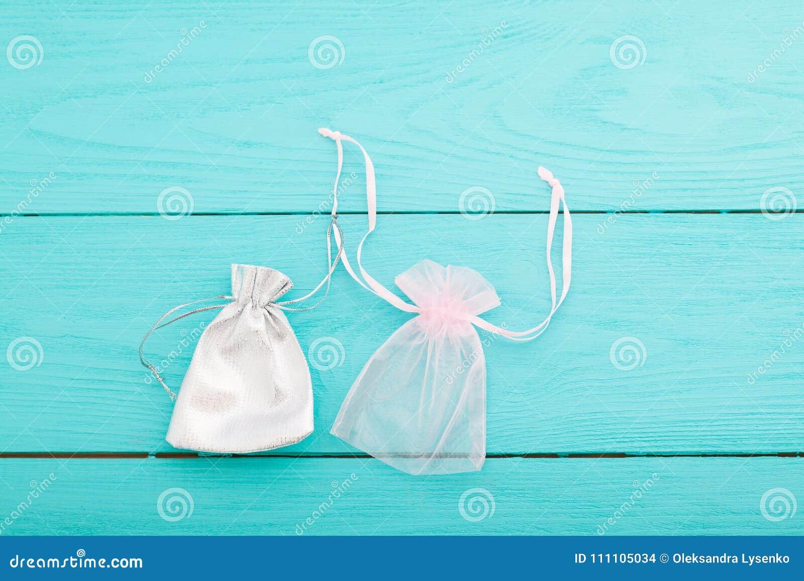Άσπρη ασημένια drawstring τσάντα στο μπλε ξύλινο υπόβαθρο Μικρή τσάντα βαμβακιού υφάσματος Σακούλα κοσμήματος Τοπ όψη Διάστημα κα