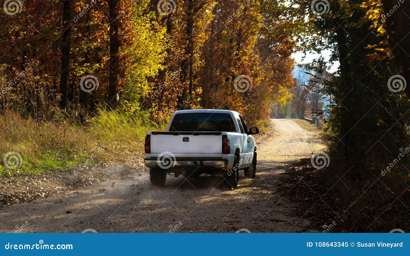 Άσπρη οδήγηση ανοιχτών φορτηγών κάτω από το σκονισμένο βρώμικο δρόμο με τα φύλλα και τη σκόνη πτώσης πίσω