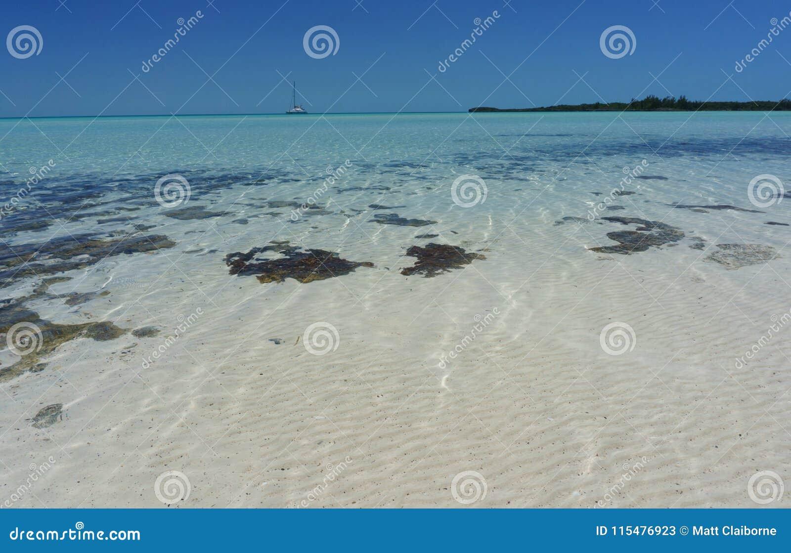Άσπρη παραλία άμμου με Sailboat