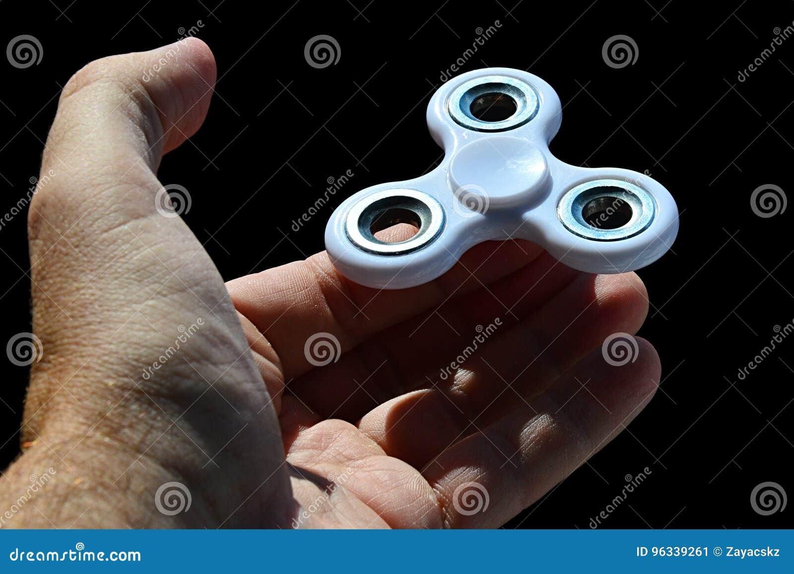 Άσπρη fidget εξισορρόπηση παιχνιδιών κλωστών στην άκρη του αντίχειρα στο φοίνικα του ενήλικου αρσενικού προσώπου, μαύρο υπόβαθρο