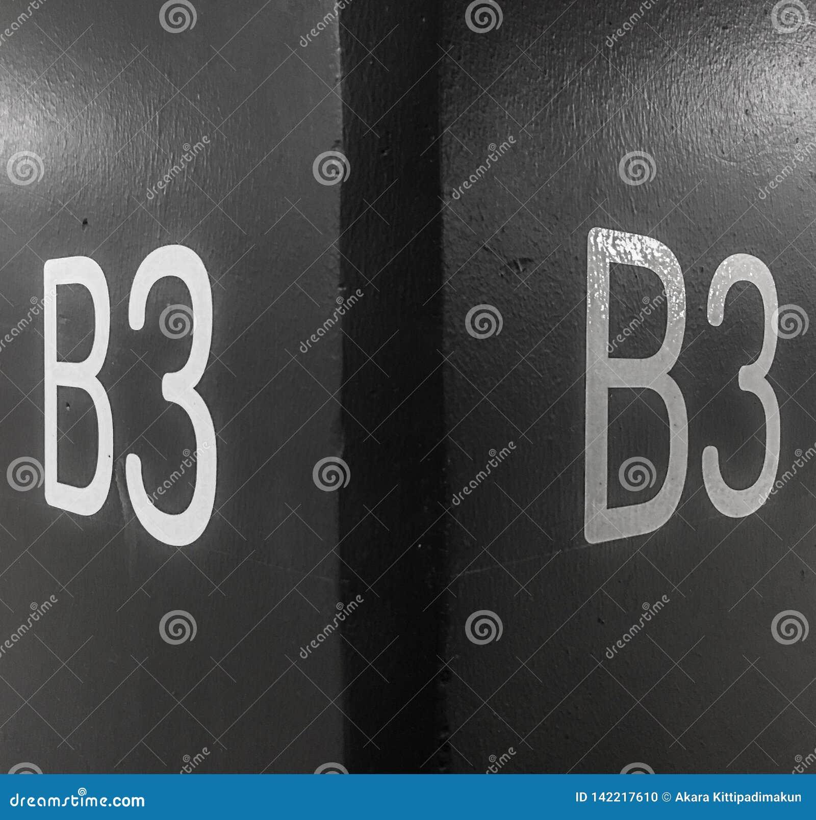 Άσπροι επιστολές και αριθμοί σε έναν μαύρο συγκεκριμένο τοίχο υποβάθρου