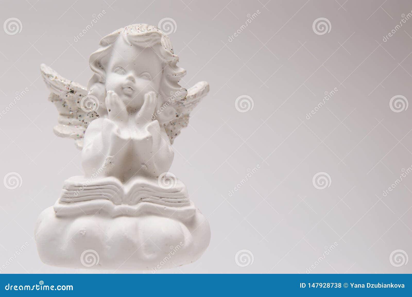 Άσπρος άγγελος γύψου σε ένα άσπρο υπόβαθρο που διαβάζει ένα βιβλίο και μια σκέψη