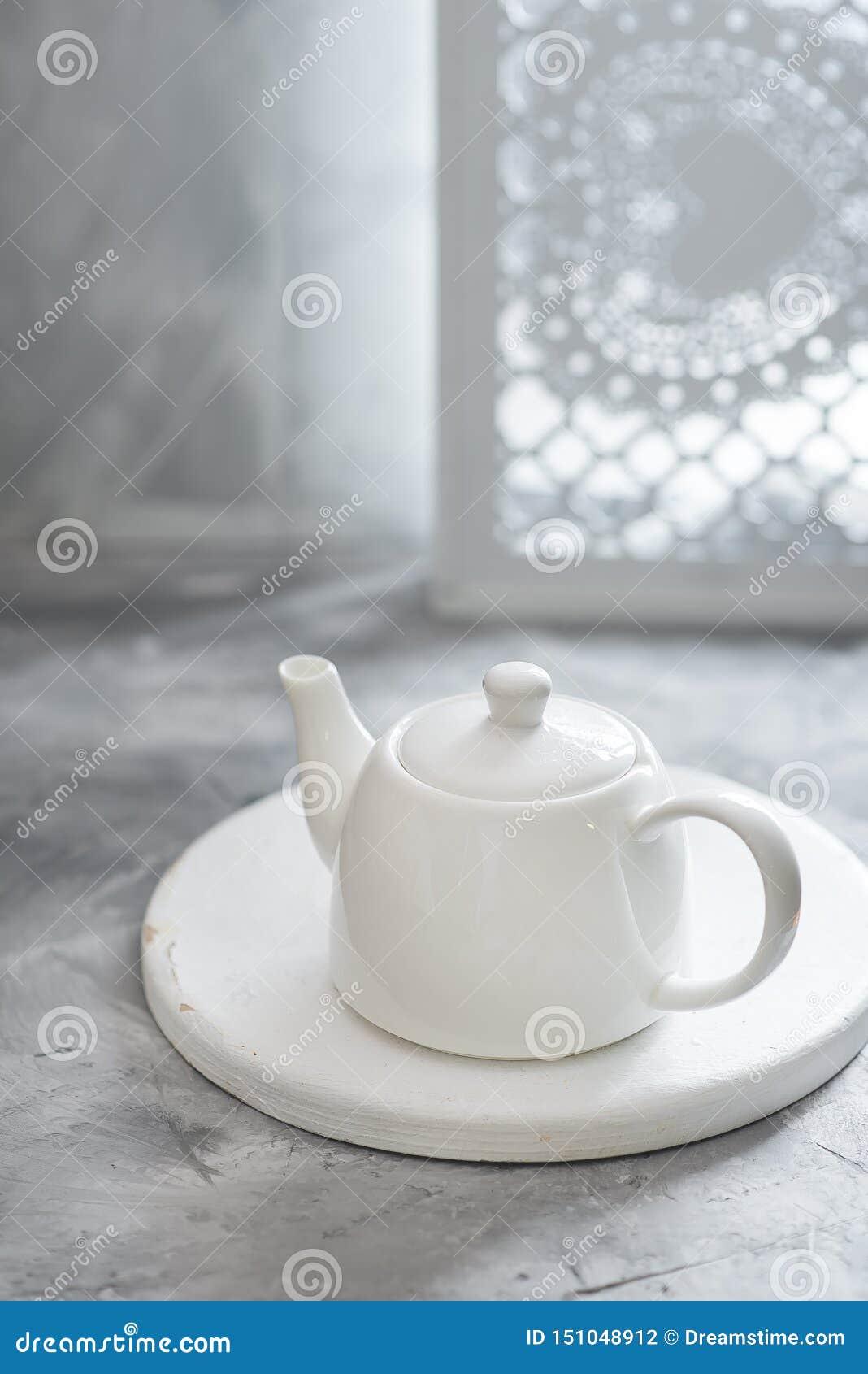 Άσπρο καθαρό teapot πορσελάνης είναι στο γκρίζο υπόβαθρο