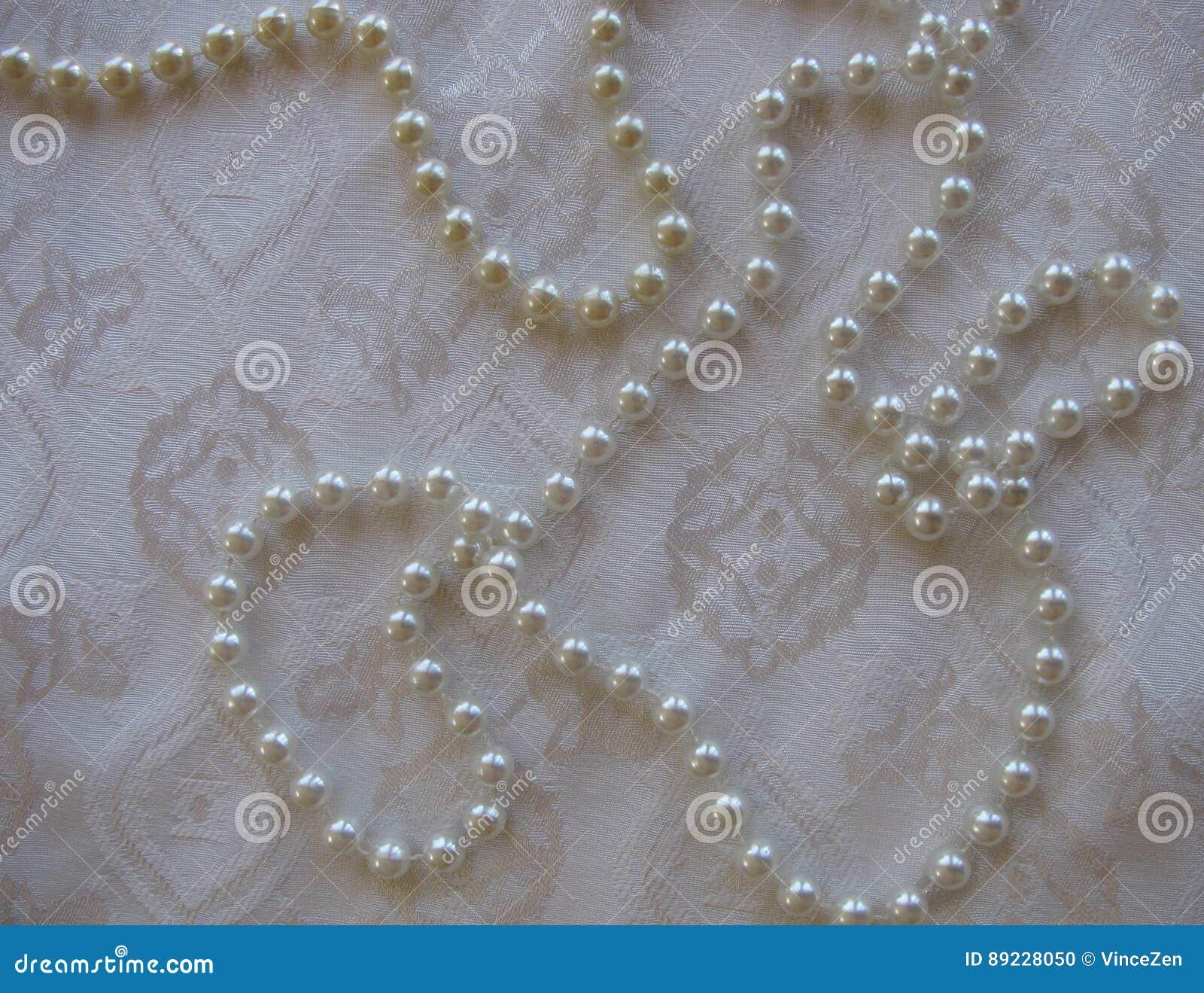 Άσπρο κατασκευασμένο υπόβαθρο των λαμπερών μαργαριταριών σε ένα πλούσιο διαμορφωμένο ύφασμα