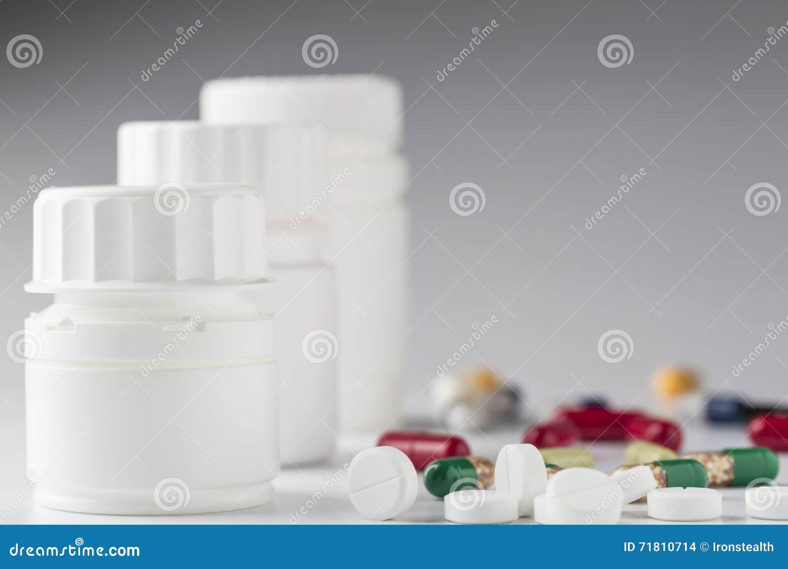 Άσπρο μπουκάλι ιατρικής και διάφορα ζωηρόχρωμα χάπια