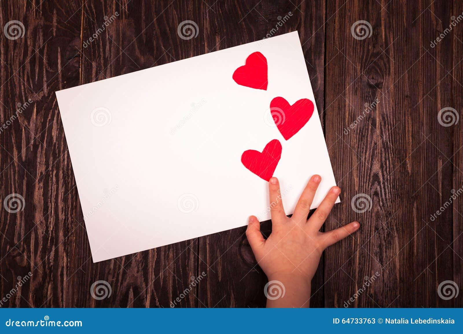 Άσπρο ξύλινο υπόβαθρο καρδιών φύλλων του εγγράφου μικρό κόκκινο
