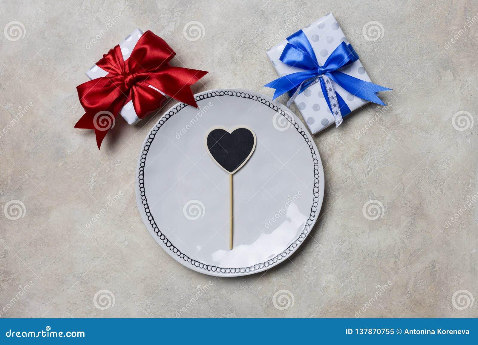 Άσπρο πιάτο με τα κιβώτια δώρων με τις κόκκινες και μπλε κορδέλλες στο άσπρο υπόβαθρο