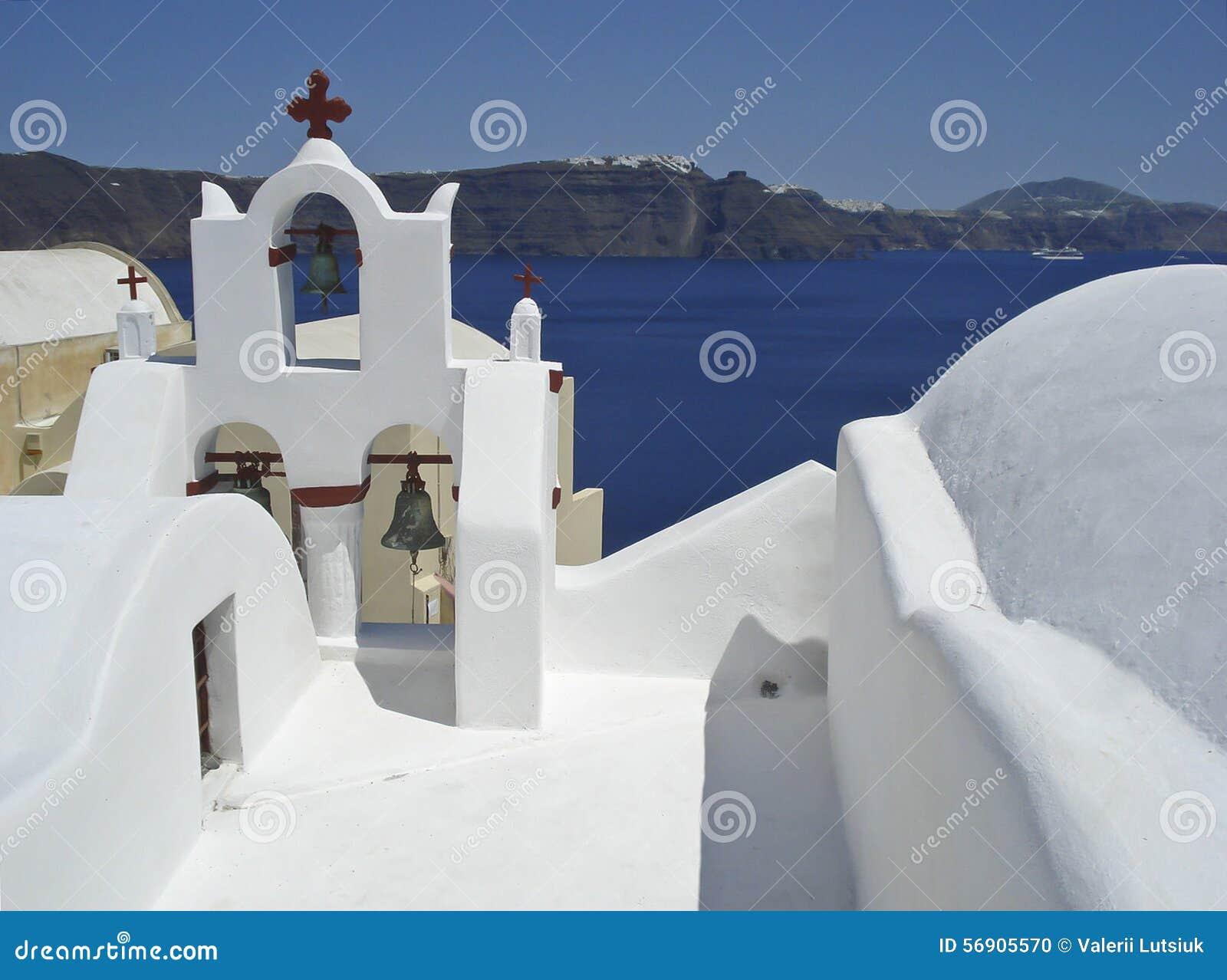 Άσπρο προαύλιο της εκκλησίας σε ένα υπόβαθρο της θάλασσας και του ουρανού (Santorini, Ελλάδα)