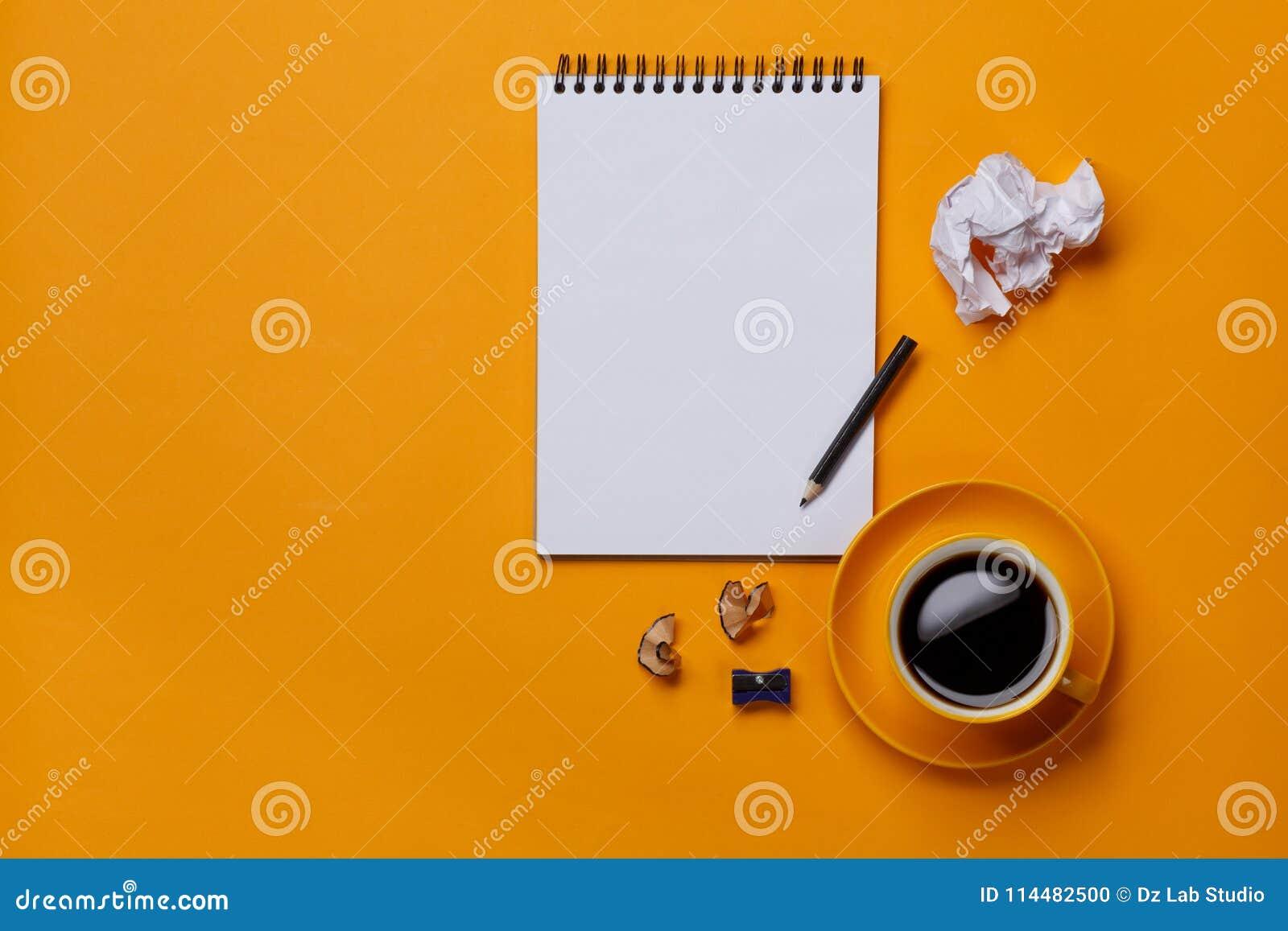 Άσπρο σημειωματάριο στο κίτρινο υπόβαθρο με το μολύβι και το έγγραφο