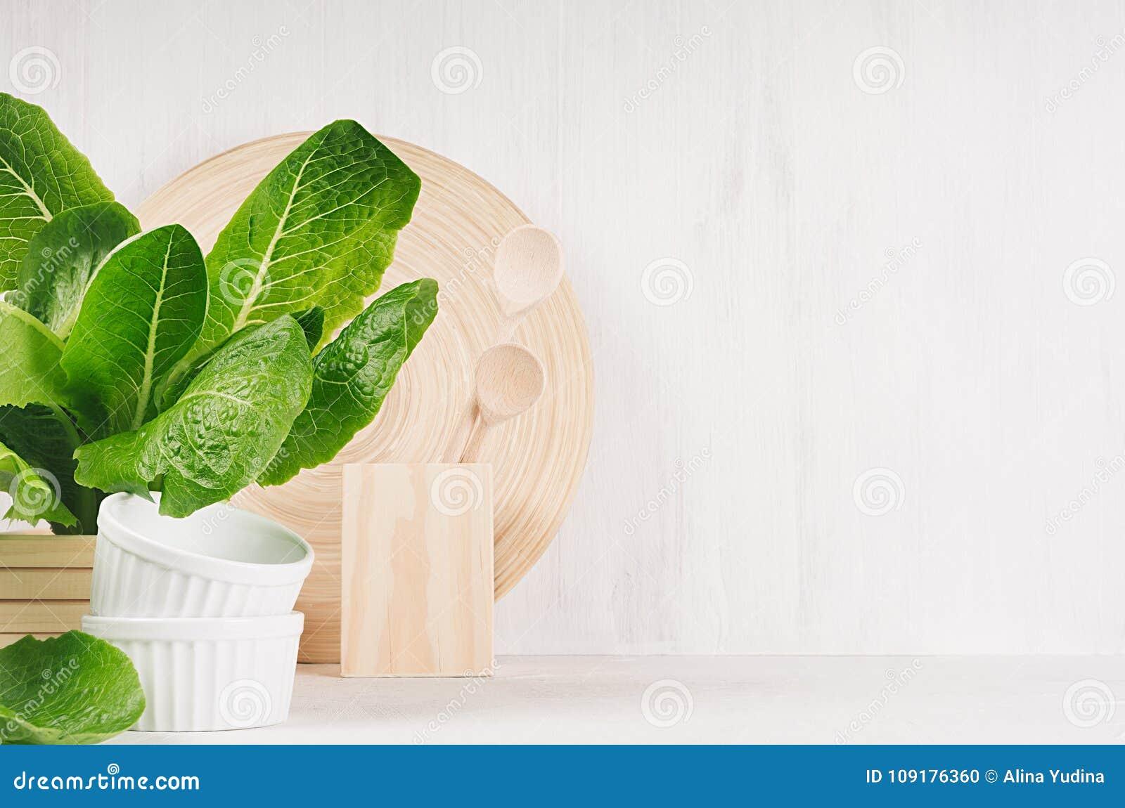 Άσπρο σύγχρονο ντεκόρ κουζινών με το μπεζ φυσικό ξύλινο πιάτο, εργαλεία, πράσινες εγκαταστάσεις στο ξύλινο υπόβαθρο