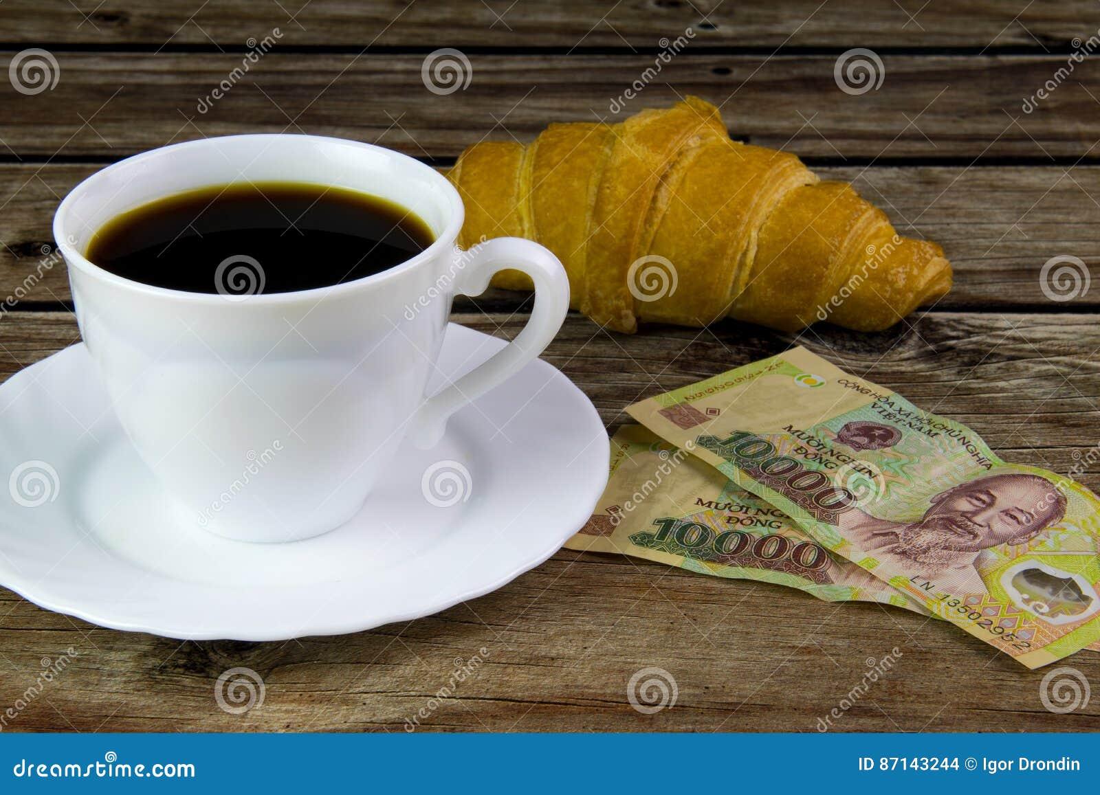 Άσπρο φλυτζάνι του μαύρου καφέ, των croissant και βιετναμέζικων χρημάτων