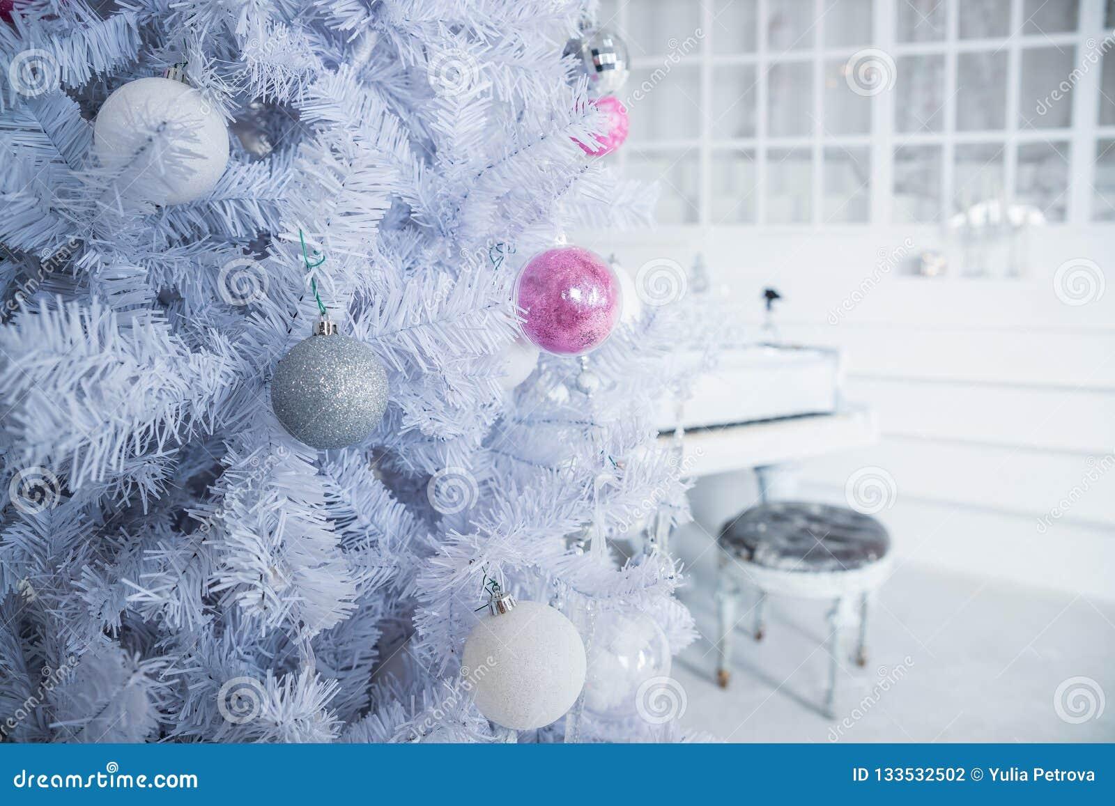 Άσπρο χριστουγεννιάτικο δέντρο που διακοσμείται με τις ασημένιες και ρόδινες διακοσμήσεις στο υπόβαθρο πιάνων καλυμμένα όρη σπιτι