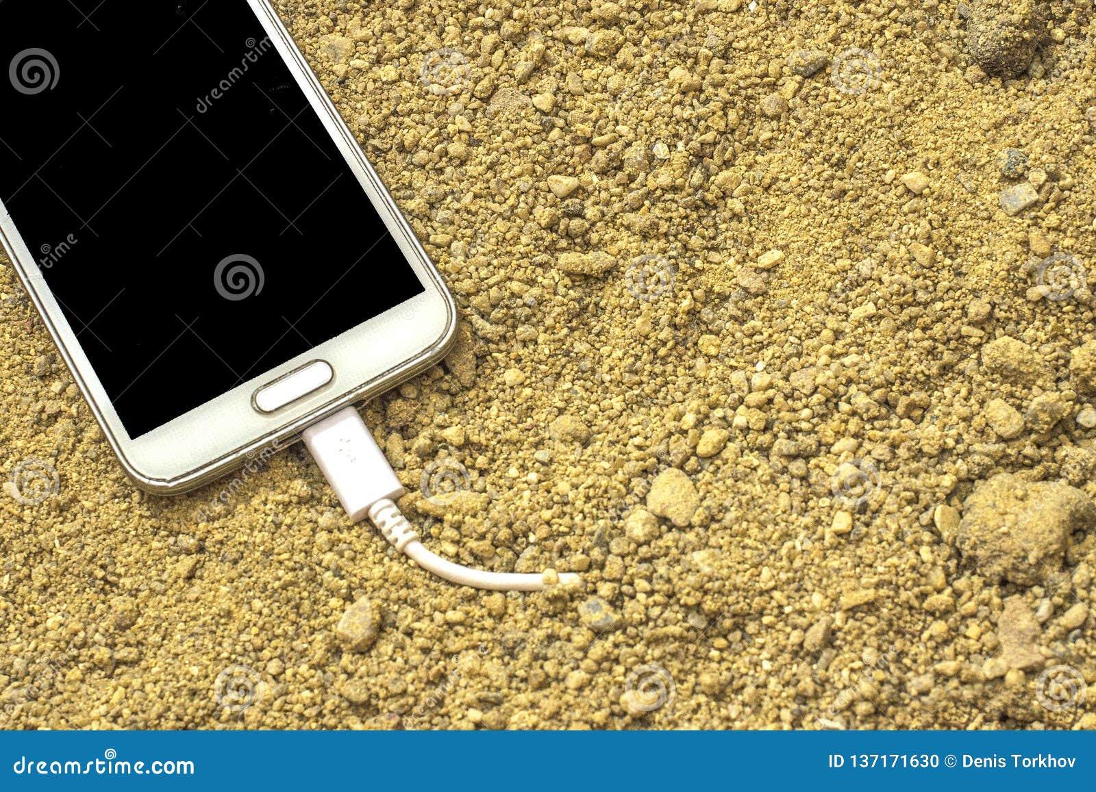 Άσπρο smartphone με έναν φορτιστή που συνδέεται με την άμμο μπροστινό και πίσω υπόβαθρο που θολώνεται