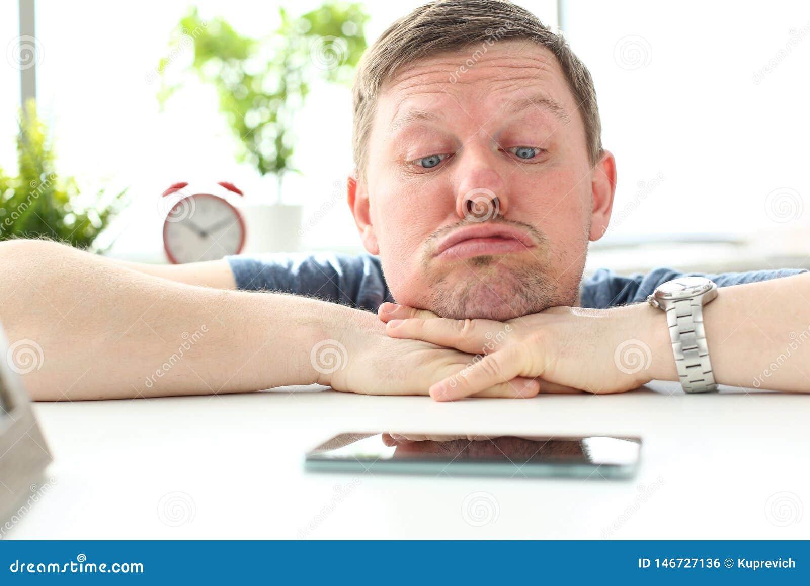 Άτομο με την αστεία έκφραση του προσώπου που κοιτάζει επίμονα στο κινητό τηλέφωνο