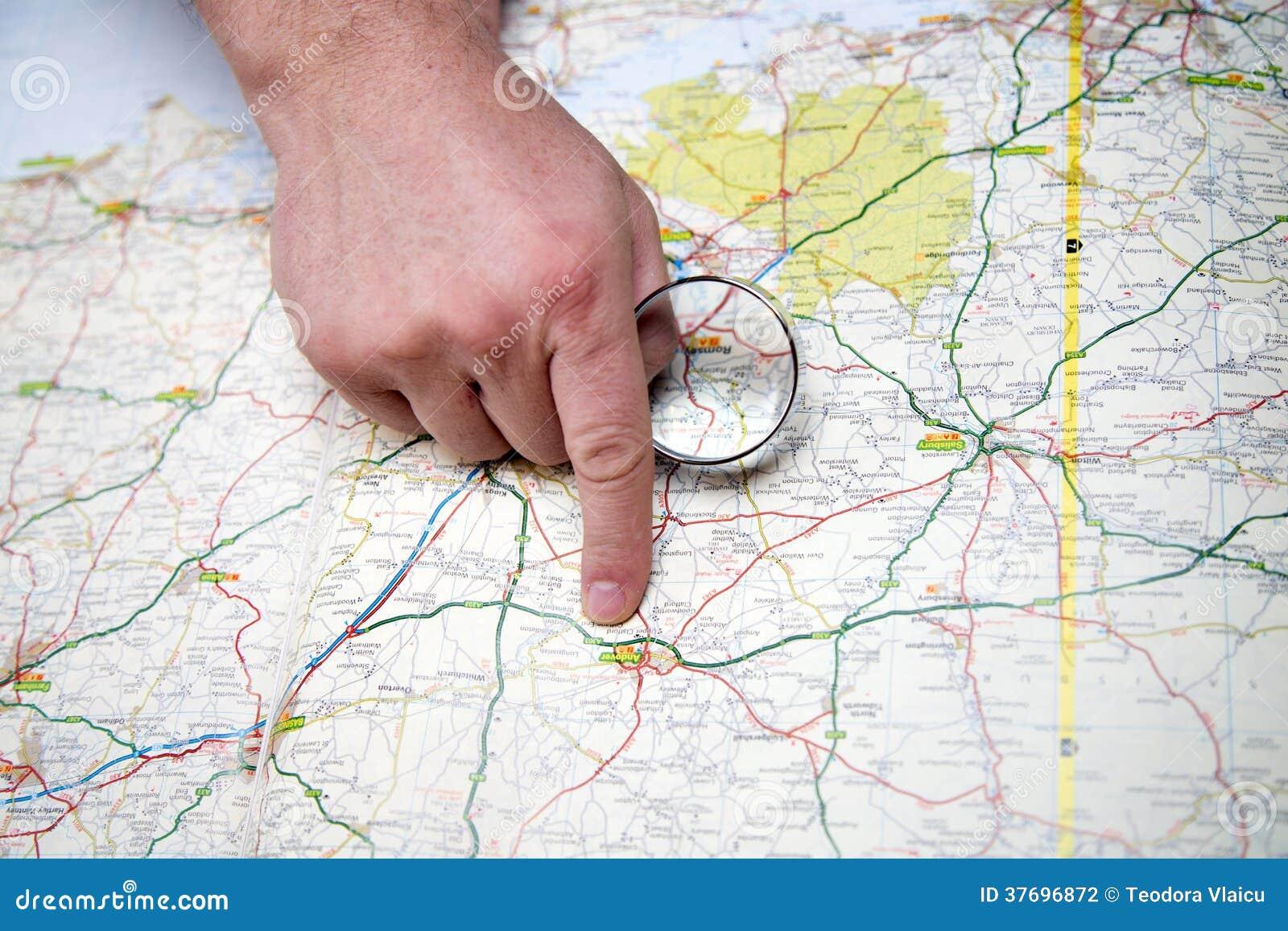 Άτομο με την πιό magnifier υπόδειξη σε έναν χάρτη
