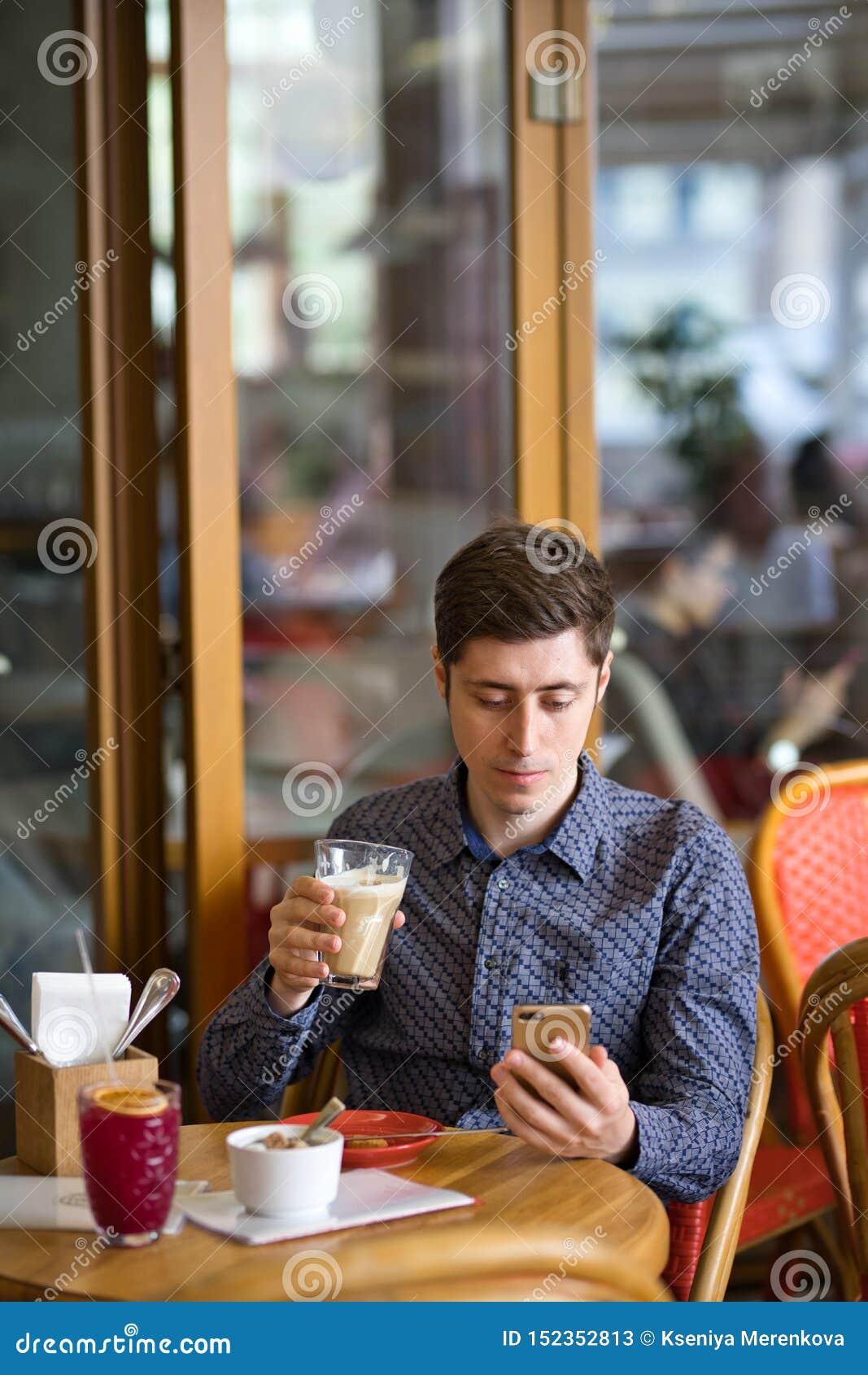 Άτομο με τον καφέ και το smartphone