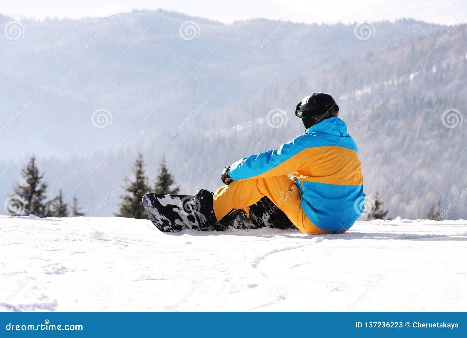Άτομο με το σνόουμπορντ που στηρίζεται στα βουνά Χειμώνας