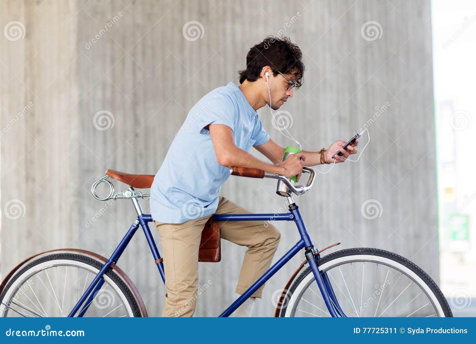 Άτομο με το smartphone και ακουστικά στο ποδήλατο