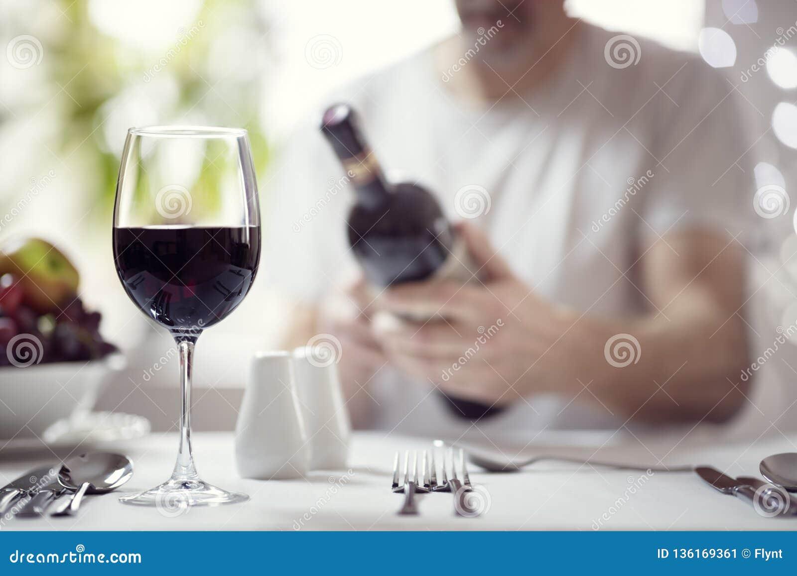 Άτομο που διαβάζει μια ετικέτα μπουκαλιών κρασιού στο εστιατόριο