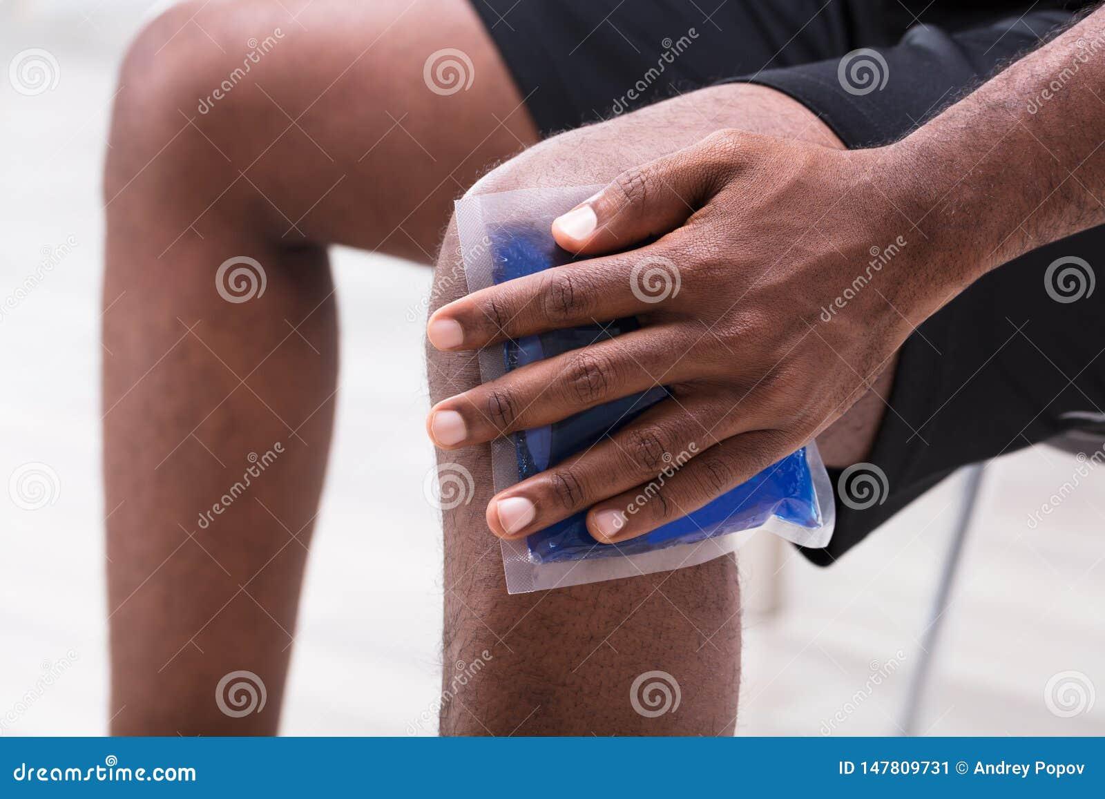 Άτομο που εφαρμόζει το πακέτο πηκτωμάτων πάγου στο γόνατό του