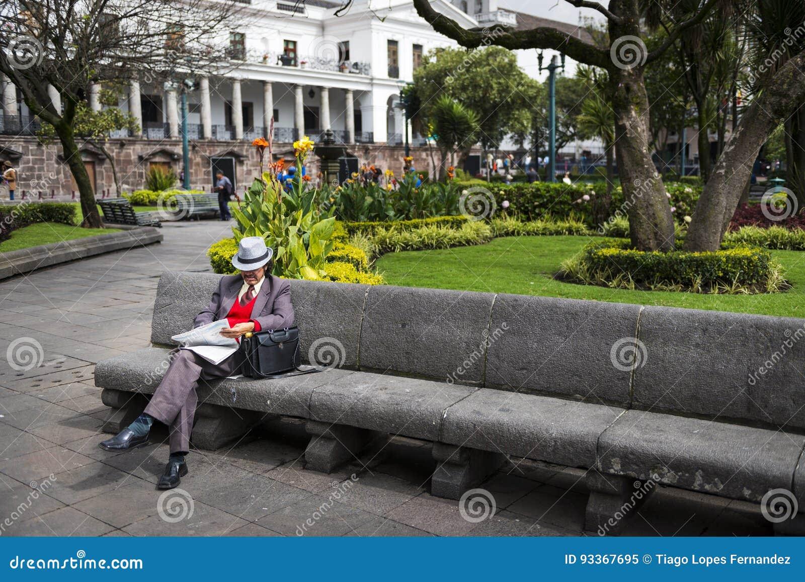 Άτομο που διαβάζει μια εφημερίδα σε έναν πάγκο σε ένα πάρκο στο τετράγωνο ανεξαρτησίας στην πόλη του Κουίτο, στον Ισημερινό