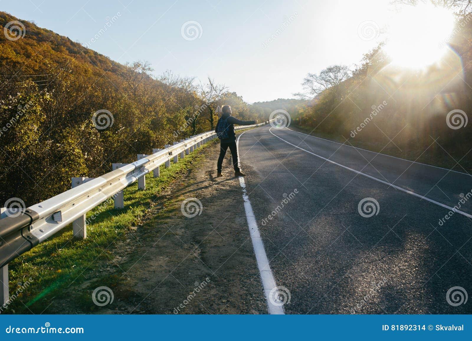 Άτομο που κάνει ωτοστόπ σε μια εθνική οδό Ταξιδιώτης που παρουσιάζει αντίχειρα επάνω επάνω για να κάνει ωτοστόπ κατά τη διάρκεια