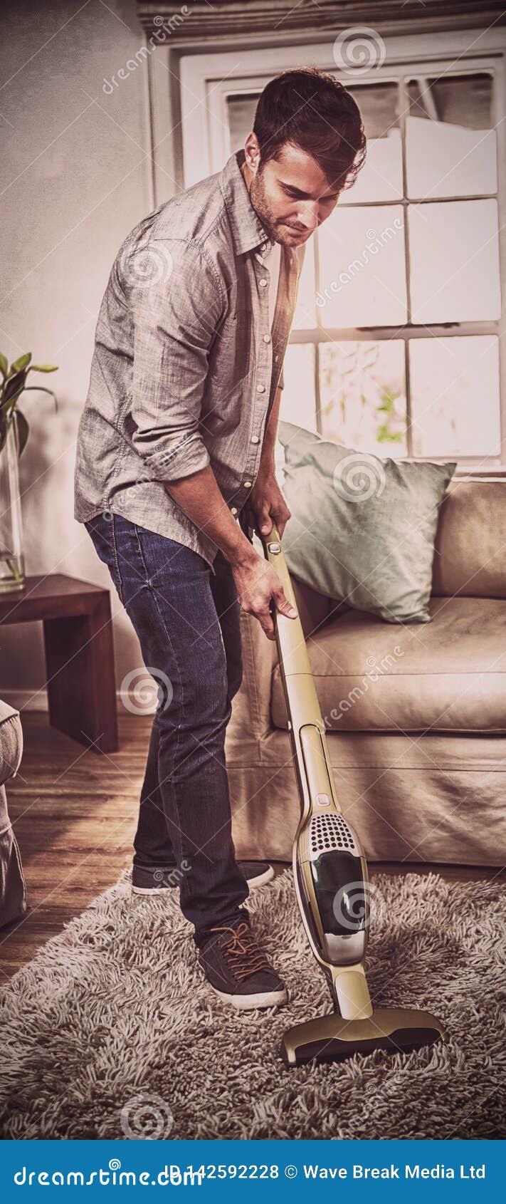 Άτομο που καθαρίζει έναν τάπητα με μια ηλεκτρική σκούπα