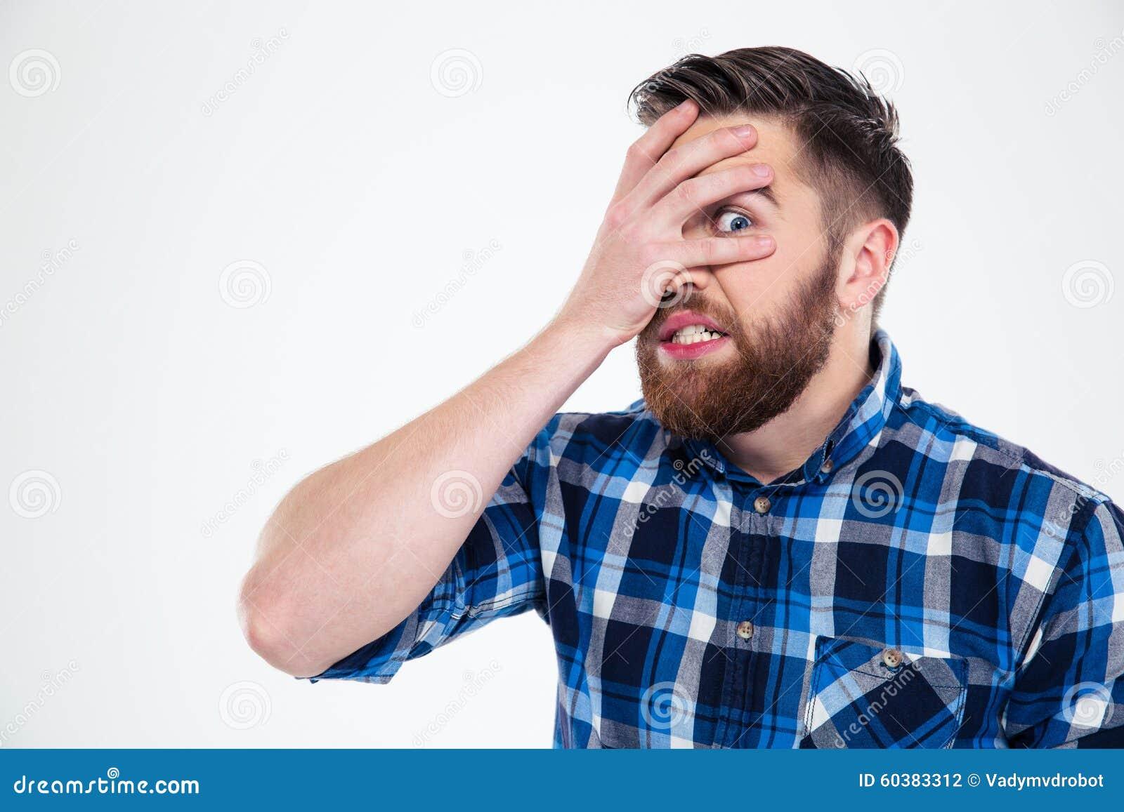 Άτομο που καλύπτει το πρόσωπό του με το φοίνικα και που εξετάζει τη κάμερα μέσω των δάχτυλων
