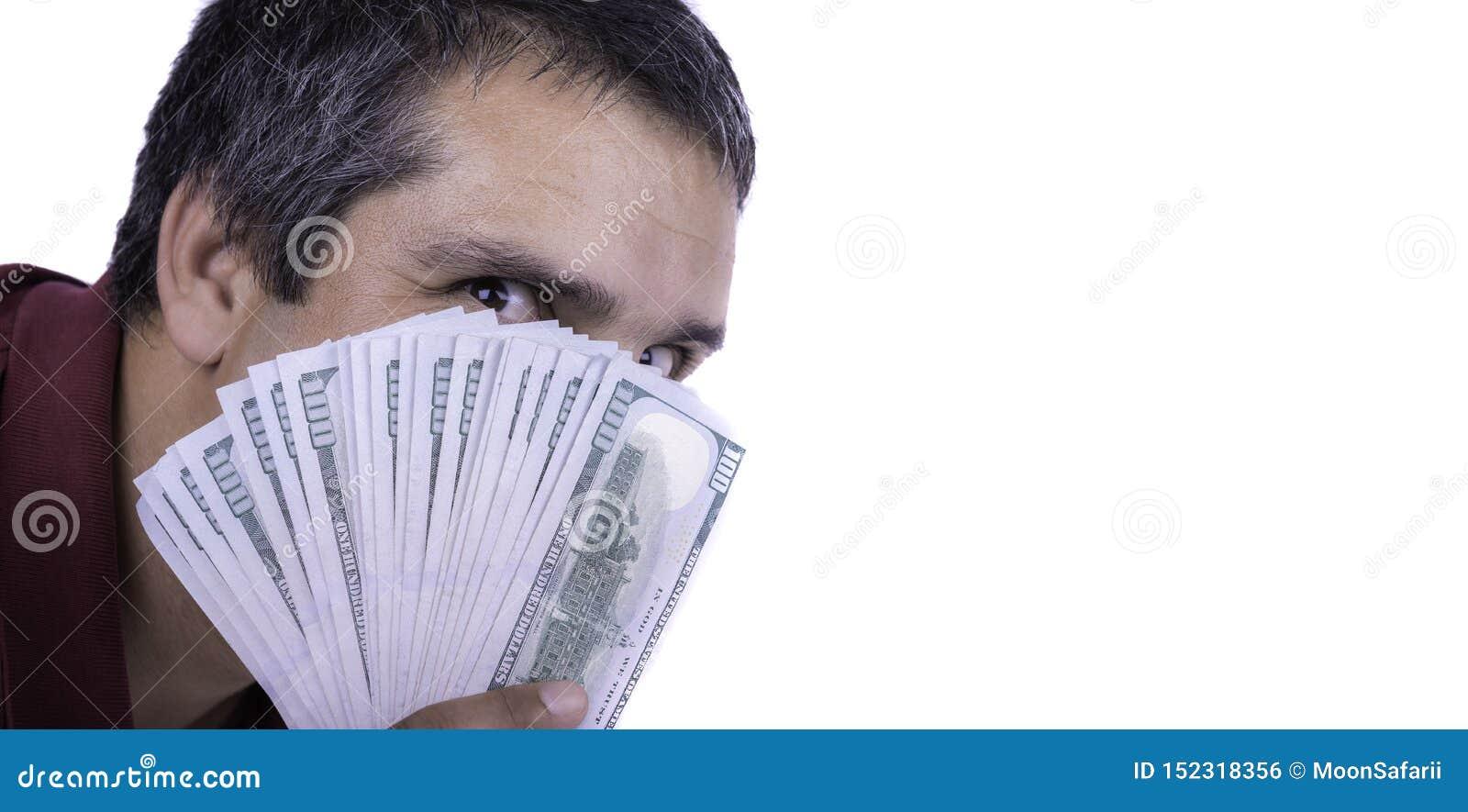 Άτομο που κρατά έναν διαδεδομένο των λογαριασμών εκατό δολαρίων που καλύπτουν το πρόσωπό του που εξετάζει άμεσα άπληστο λάγνο ικα