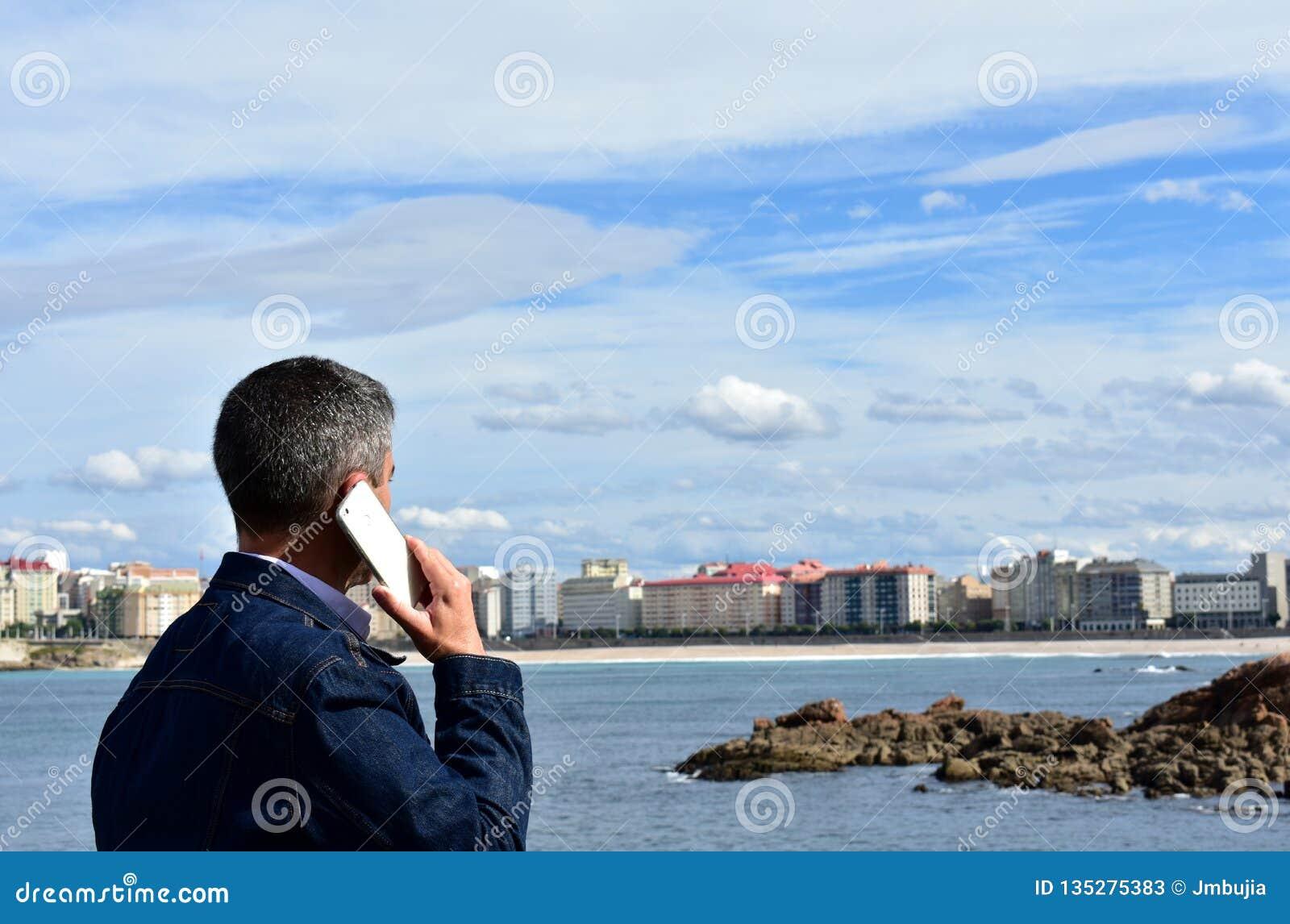 Άτομο που μιλά σε ένα smartphone σε έναν κόλπο Άποψη παραλιών, περιπάτων και πόλεων