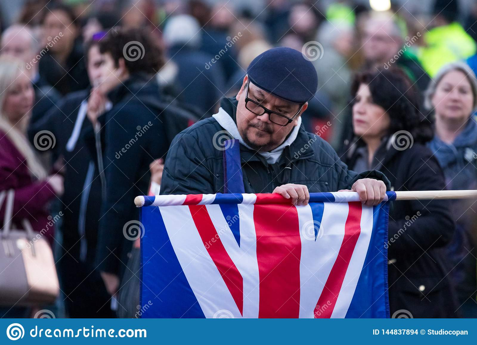 Άτομο που ξετυλίγει τη σημαία του Union Jack στο πλήθος πλατειών Τραφάλγκα