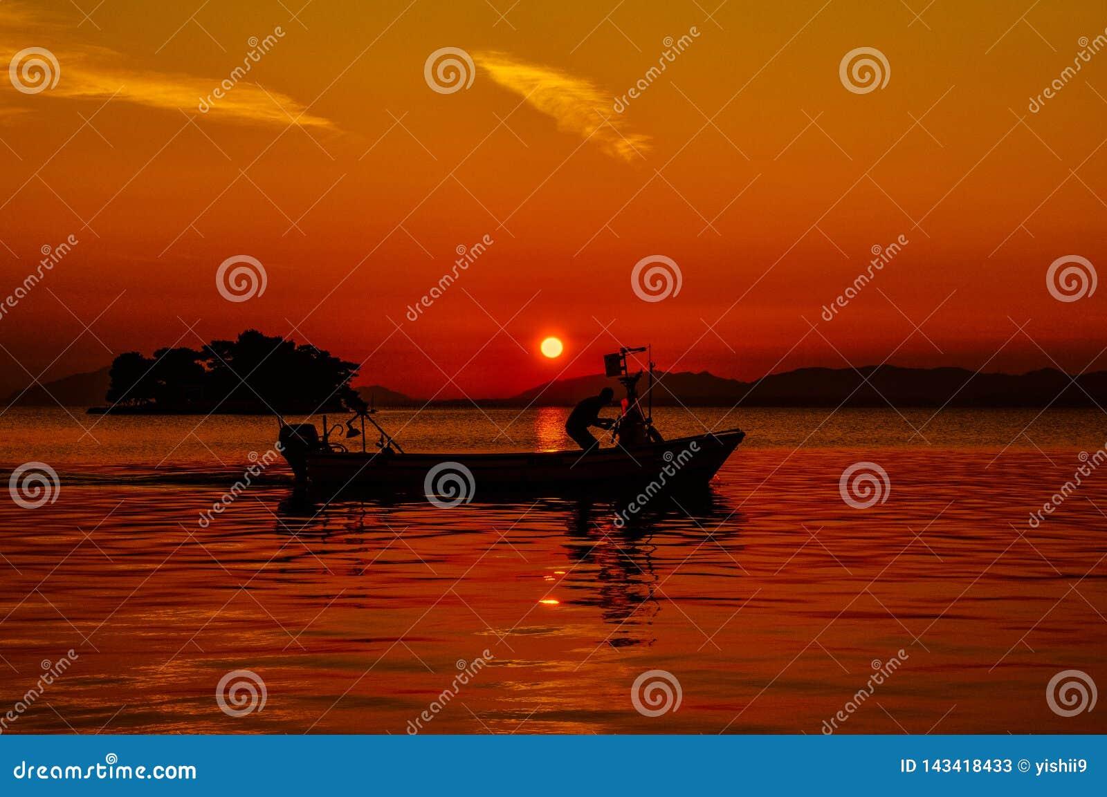 Άτομο που οδηγεί μια βάρκα με τον ήλιο ρύθμισης στο υπόβαθρο