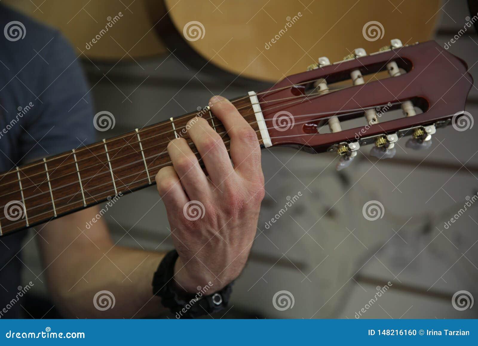 Άτομο που παίζει μια κλασική κιθάρα Μαζεύει με το χέρι επάνω τις σειρές στην κιθάρα