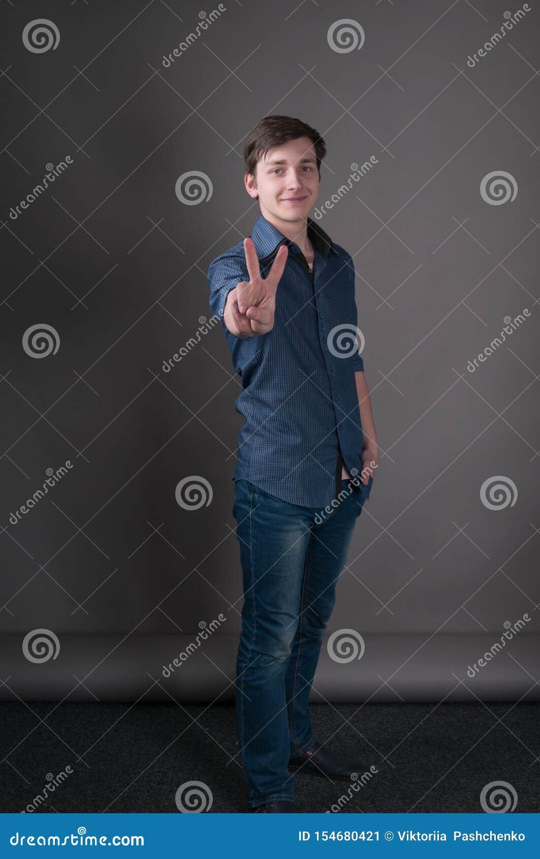 Άτομο που παρουσιάζει σημάδι νίκης με τα δάχτυλα, που χαμογελά και που εξετάζει τη κάμερα