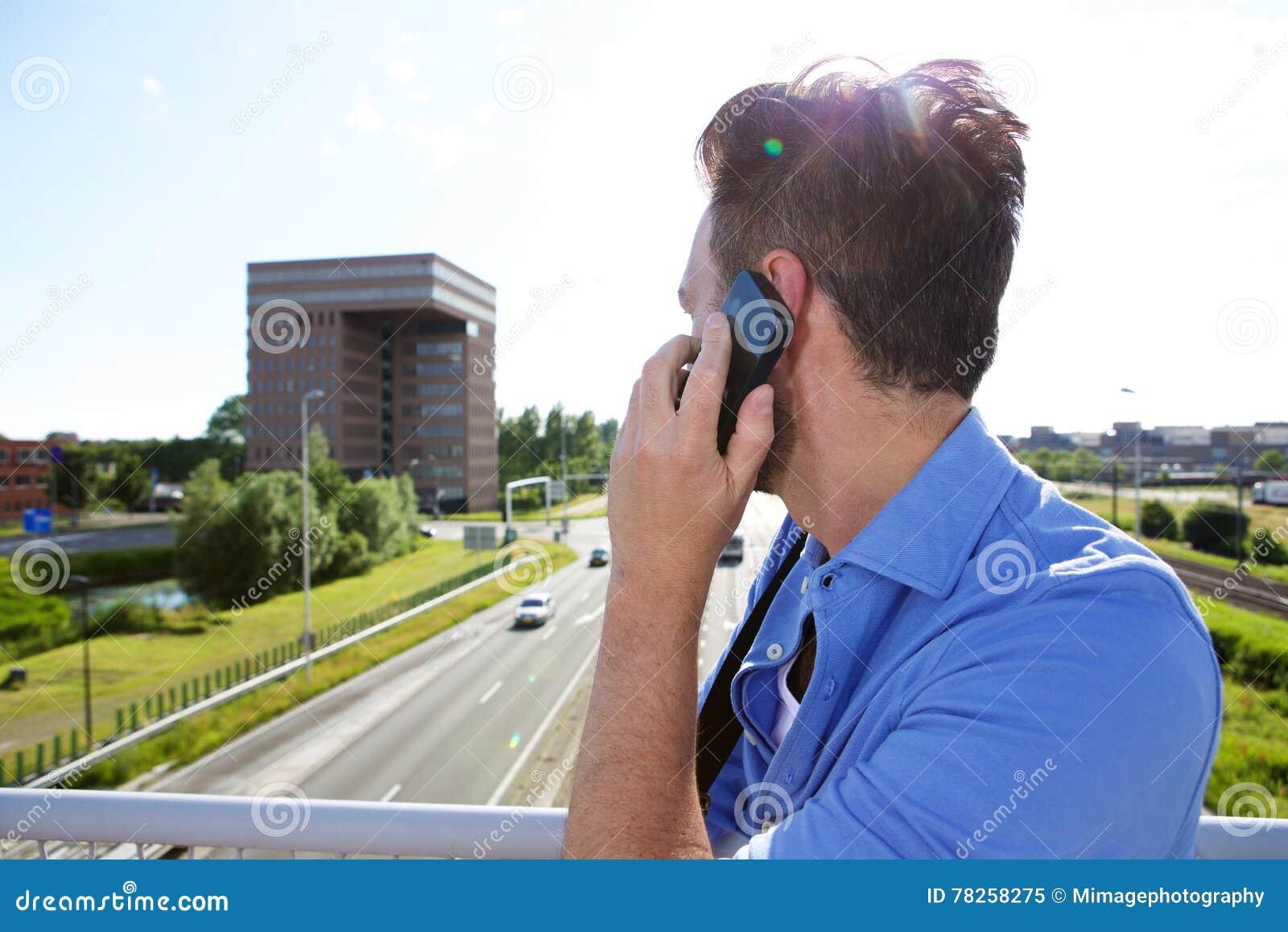 Άτομο που στέκεται στη γέφυρα και που μιλά στο κινητό τηλέφωνο