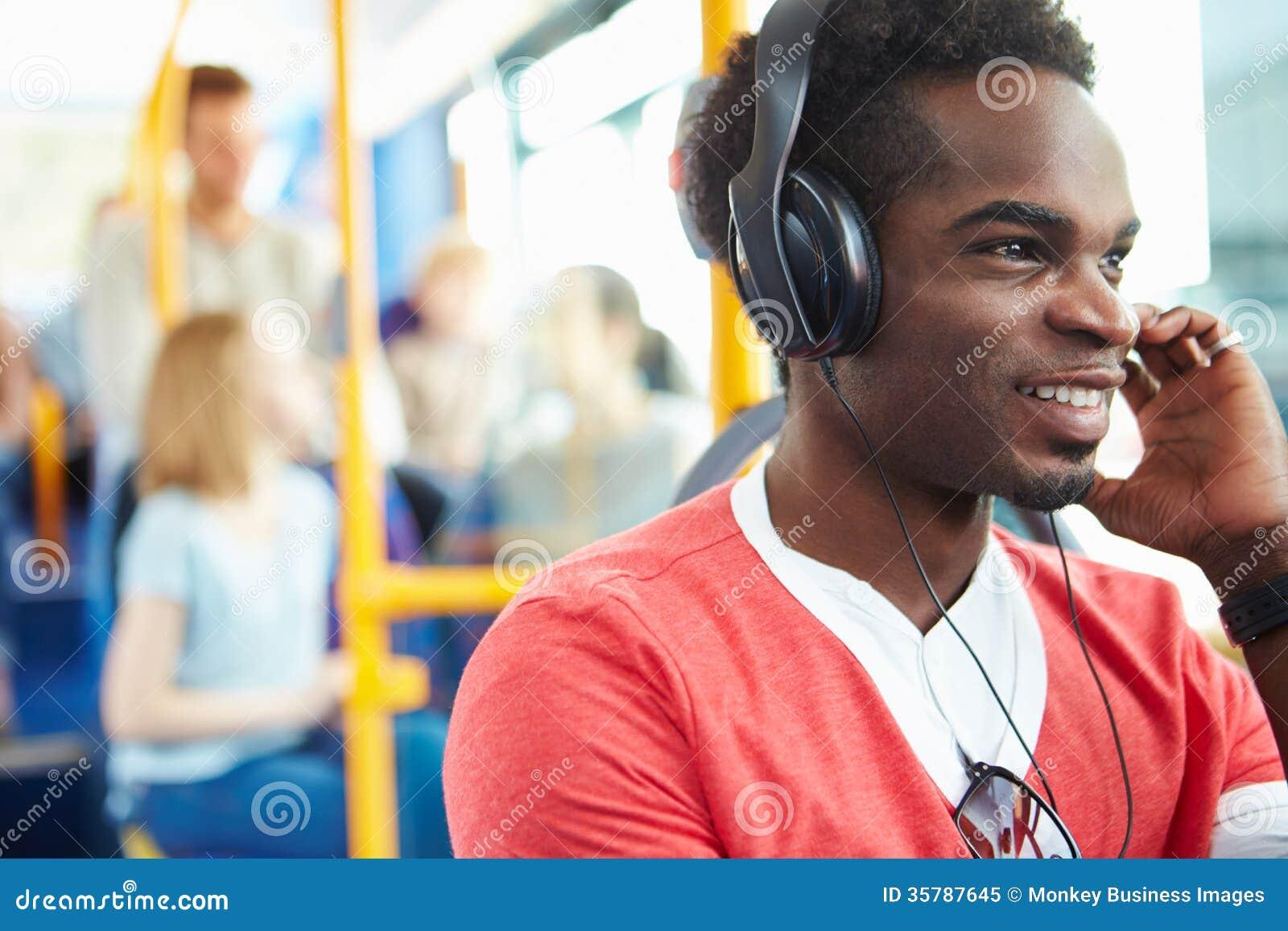 Άτομο που φορά τα ακουστικά που ακούνε τη μουσική στο ταξίδι λεωφορείων