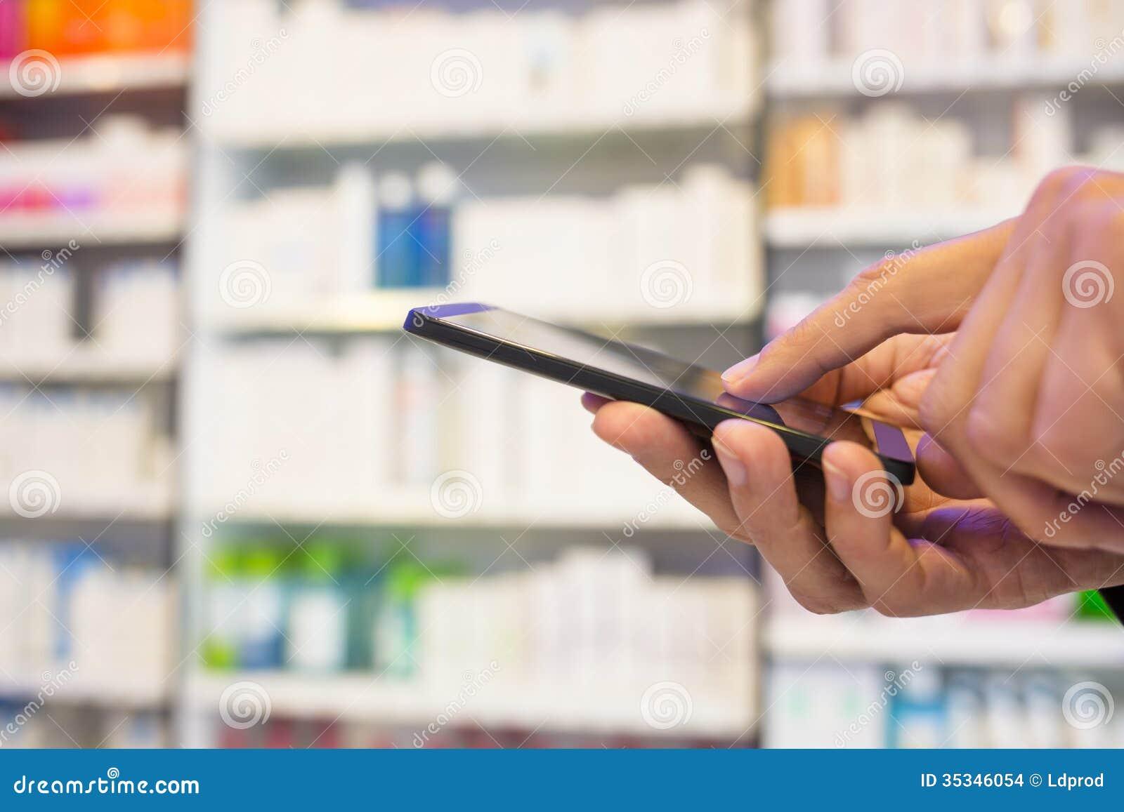 Άτομο που χρησιμοποιεί ένα κινητό τηλέφωνο στο φαρμακείο