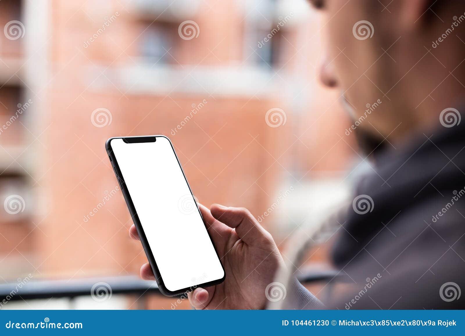 Άτομο που χρησιμοποιεί σύγχρονο κινητό bezel smartphone λιγότερο σχέδιο Πυροβοληθείς με την άποψη τρίτος-προσώπων, κενή οθόνη