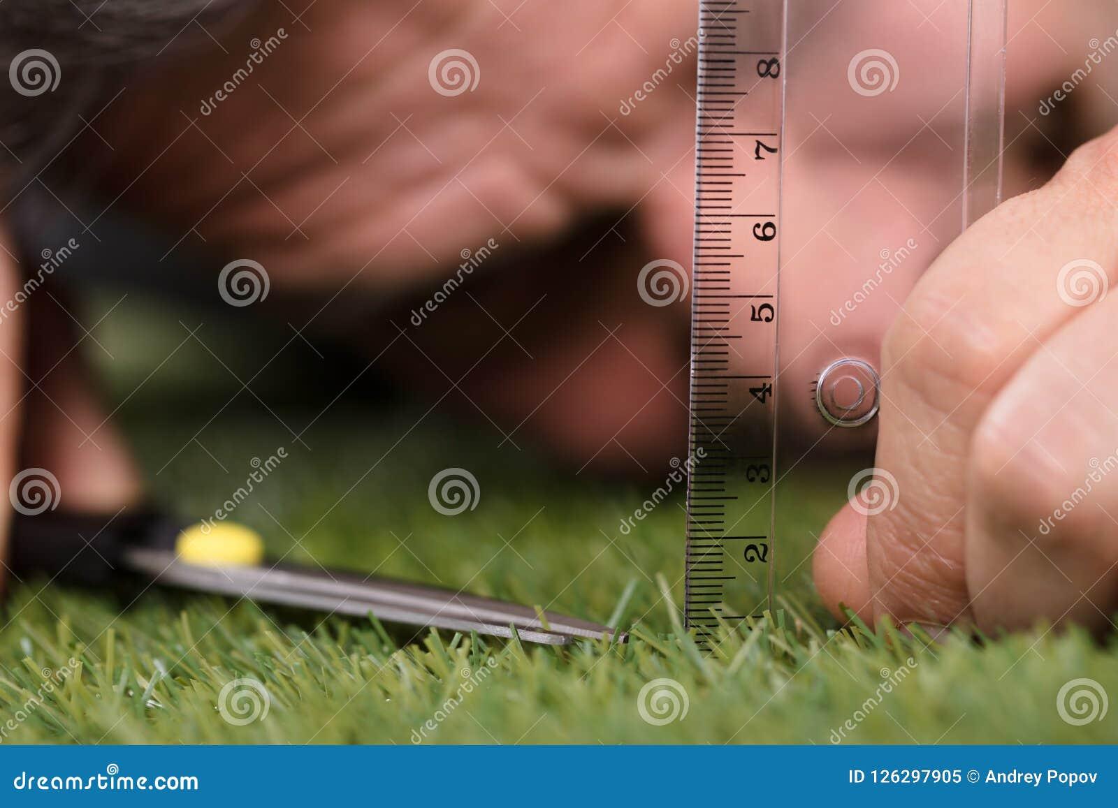 Άτομο που χρησιμοποιεί την κλίμακα μέτρησης κόβοντας τη χλόη